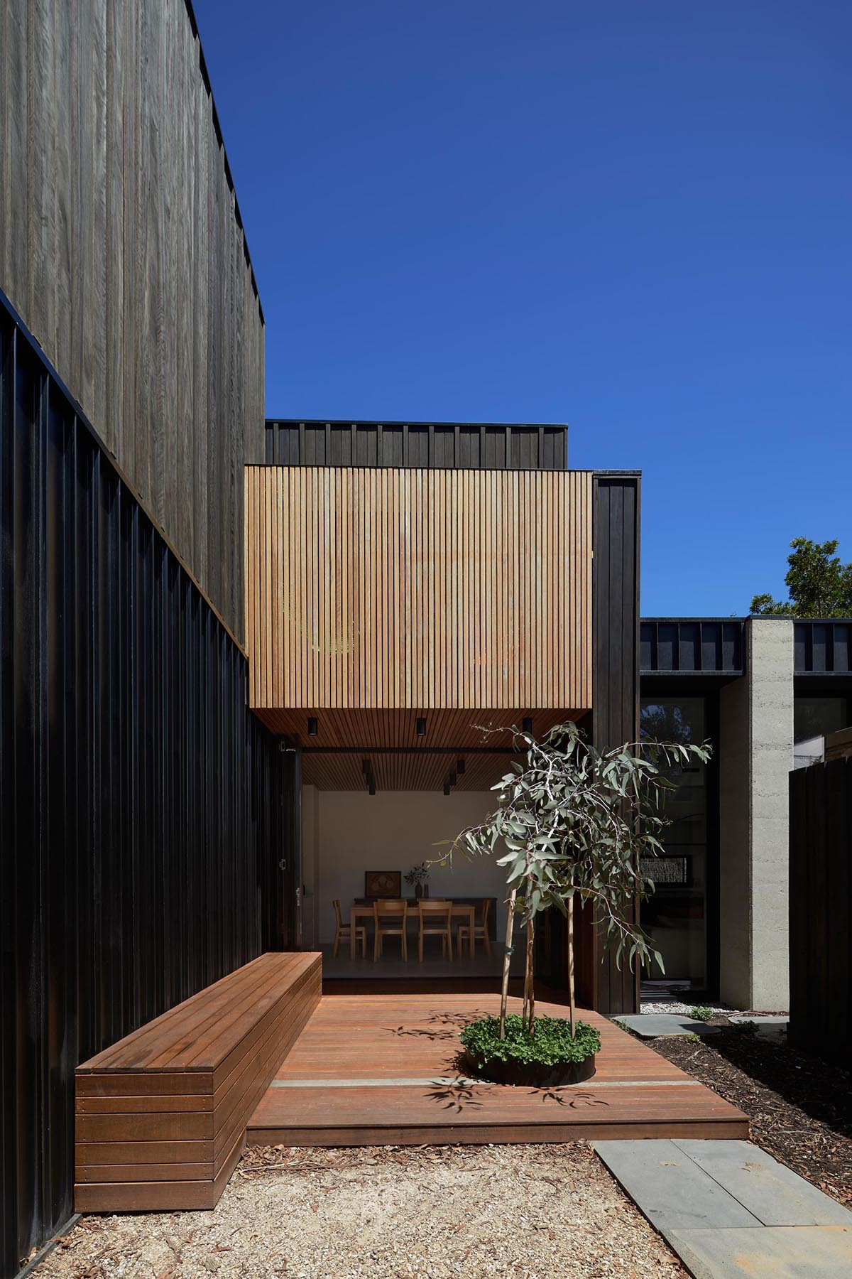 A modern home with dark wood and concrete exterior, and a deck with built-in bench made from lighting wood.