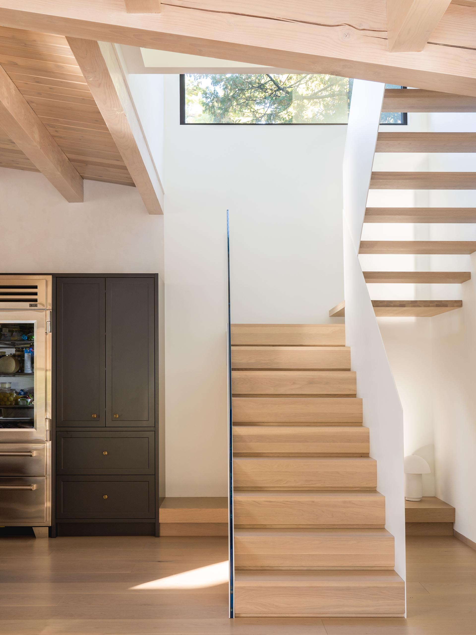 Modern white stairs with wood treads and a glass handrail.
