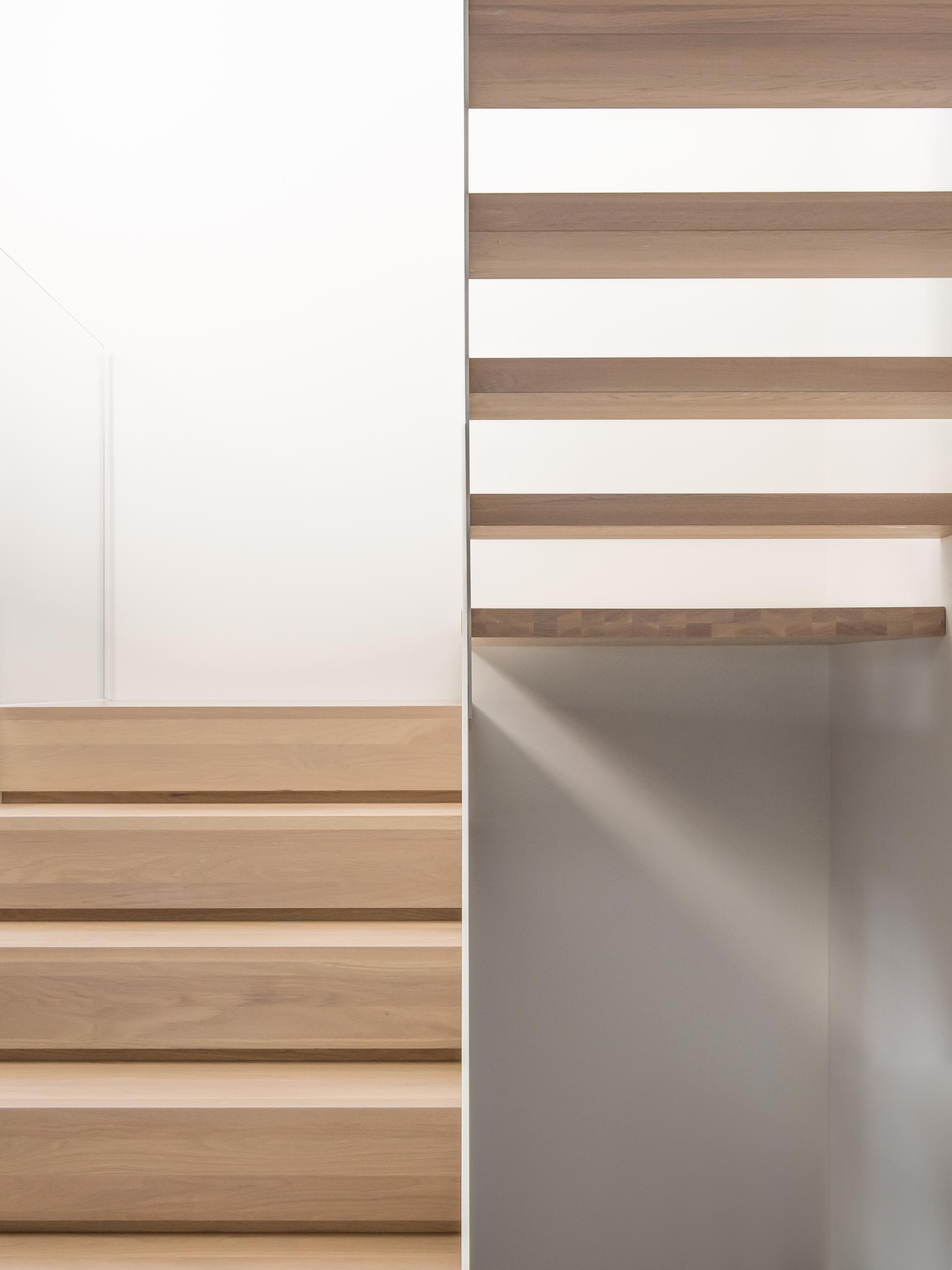 Modern white staircase with wood treads.