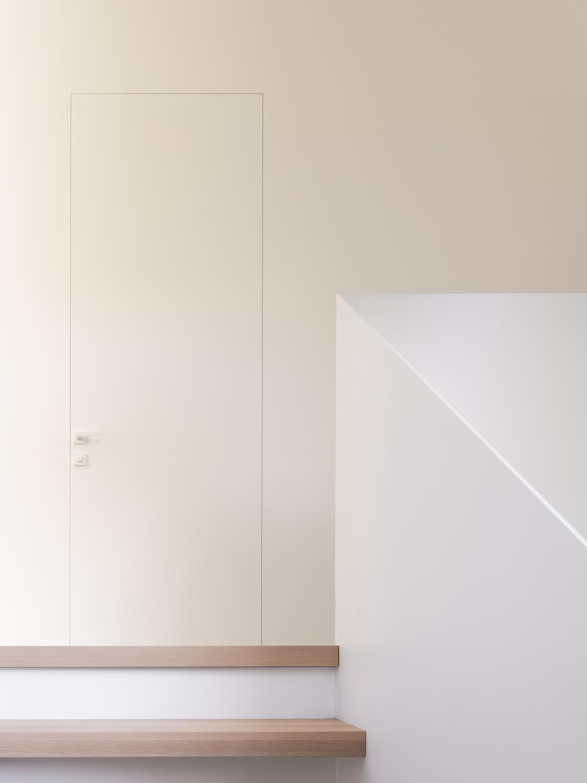 A minimalist door frame blends the door into the wall.