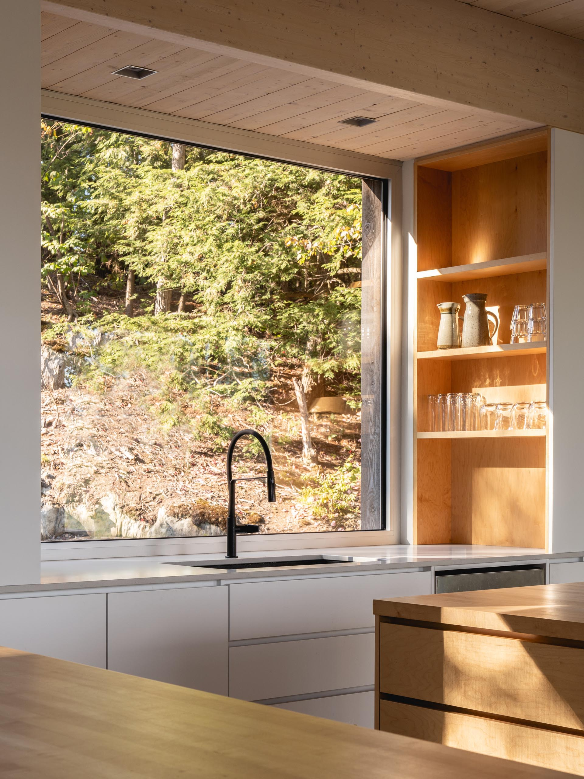 In this modern kitchen, there's two kitchen islands made from solid maple, polished concrete floors, and a large square window above the sink.