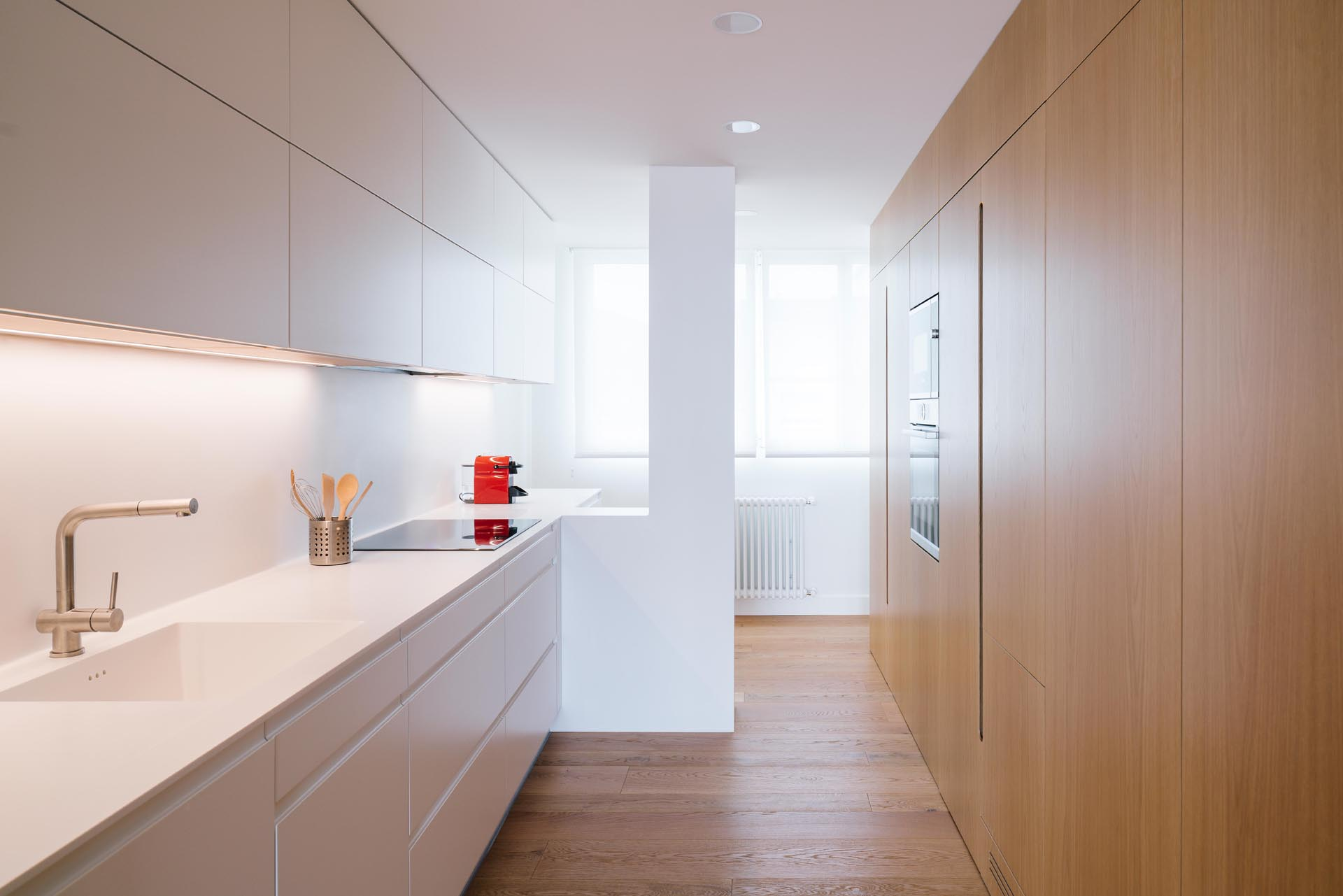 A modern kitchen with minimalist white and wood cabinets.