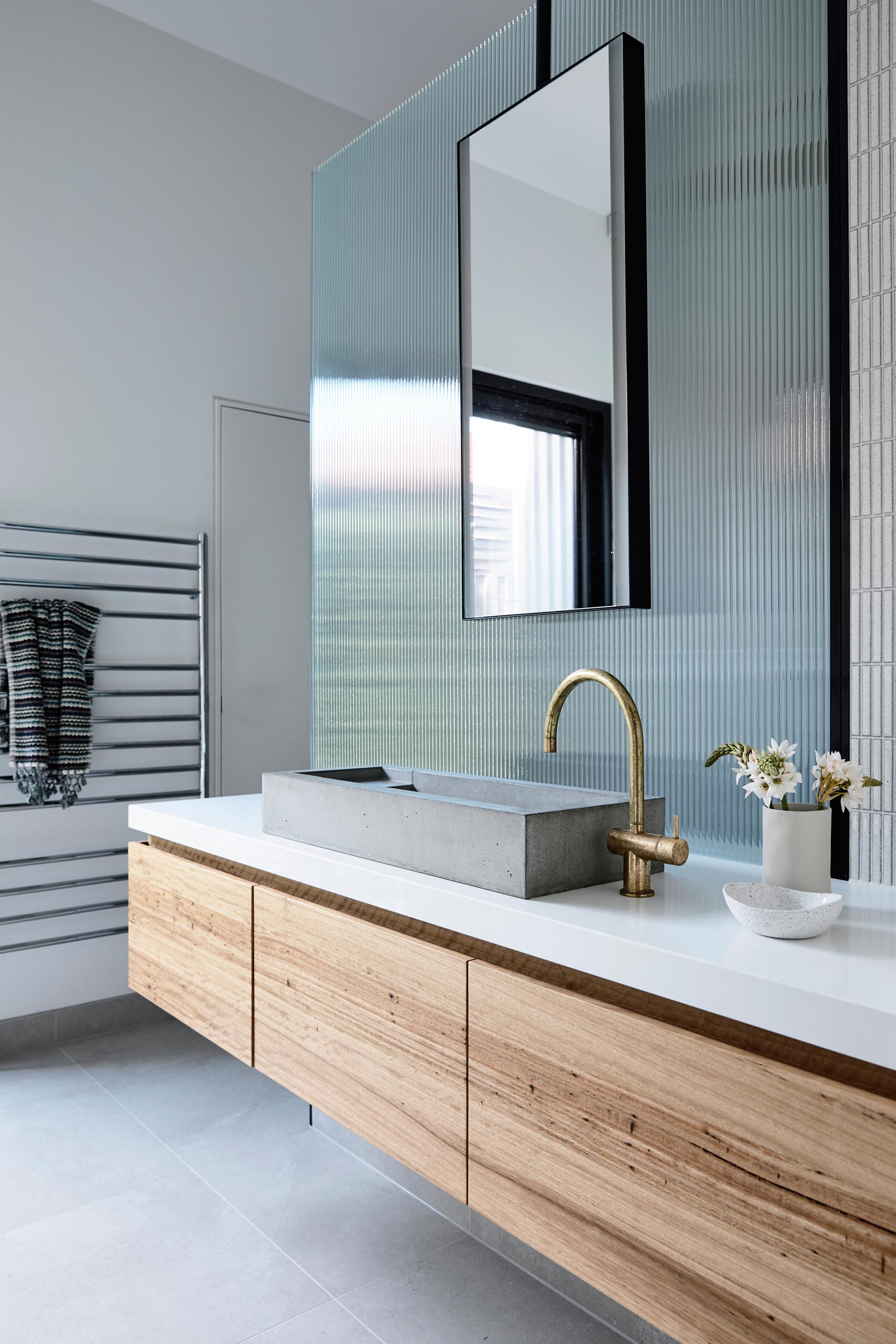 A modern bathroom with a long wood vanity, a concrete sink, bronze faucet, and a textured glass panel that hides the shower.