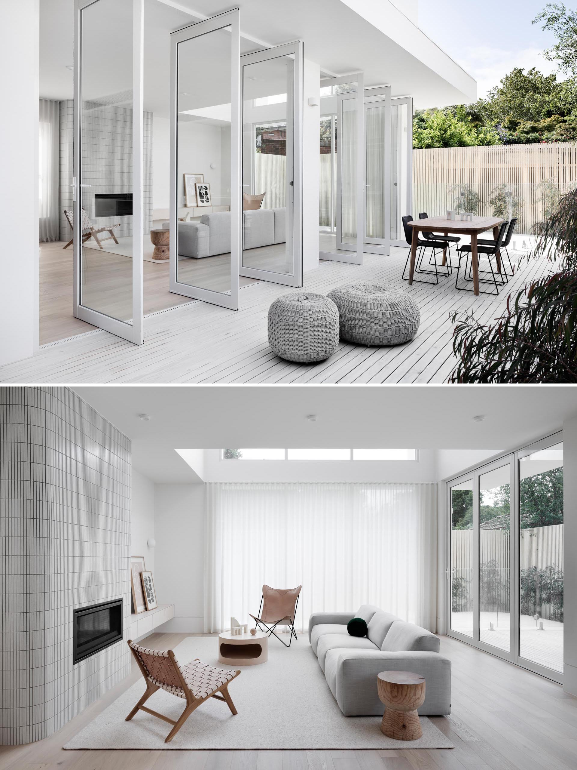 This modern house features pivoting glass doors, and and interior with a white tiled fireplace surround in the living room, a dining room with a light wood table, and a kitchen with minimalist cabinets and a white island.
