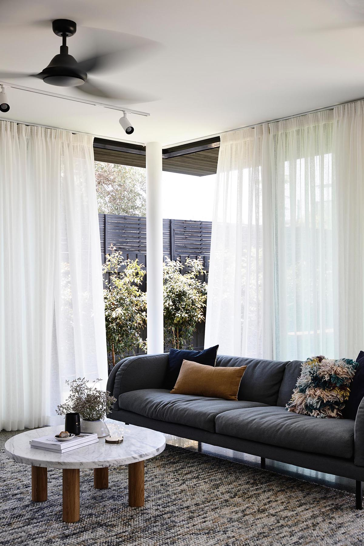 The glass walls of this modern home can be opened to connect the interior spaces, like the living room, to the backyard. Floor to ceiling curtains allow the breeze to flow through, yet provide privacy at the same time.