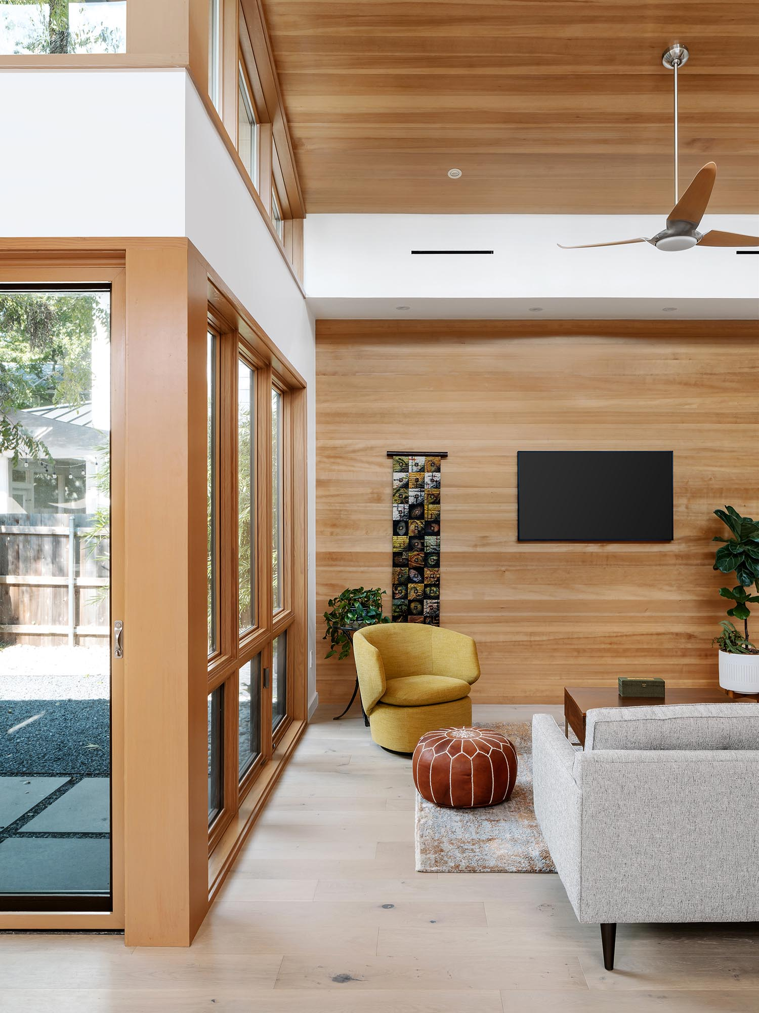 In this modern living room, a high sloped ceiling creates a lofty and open environment, while the wood adds a sense of warmth to the space.