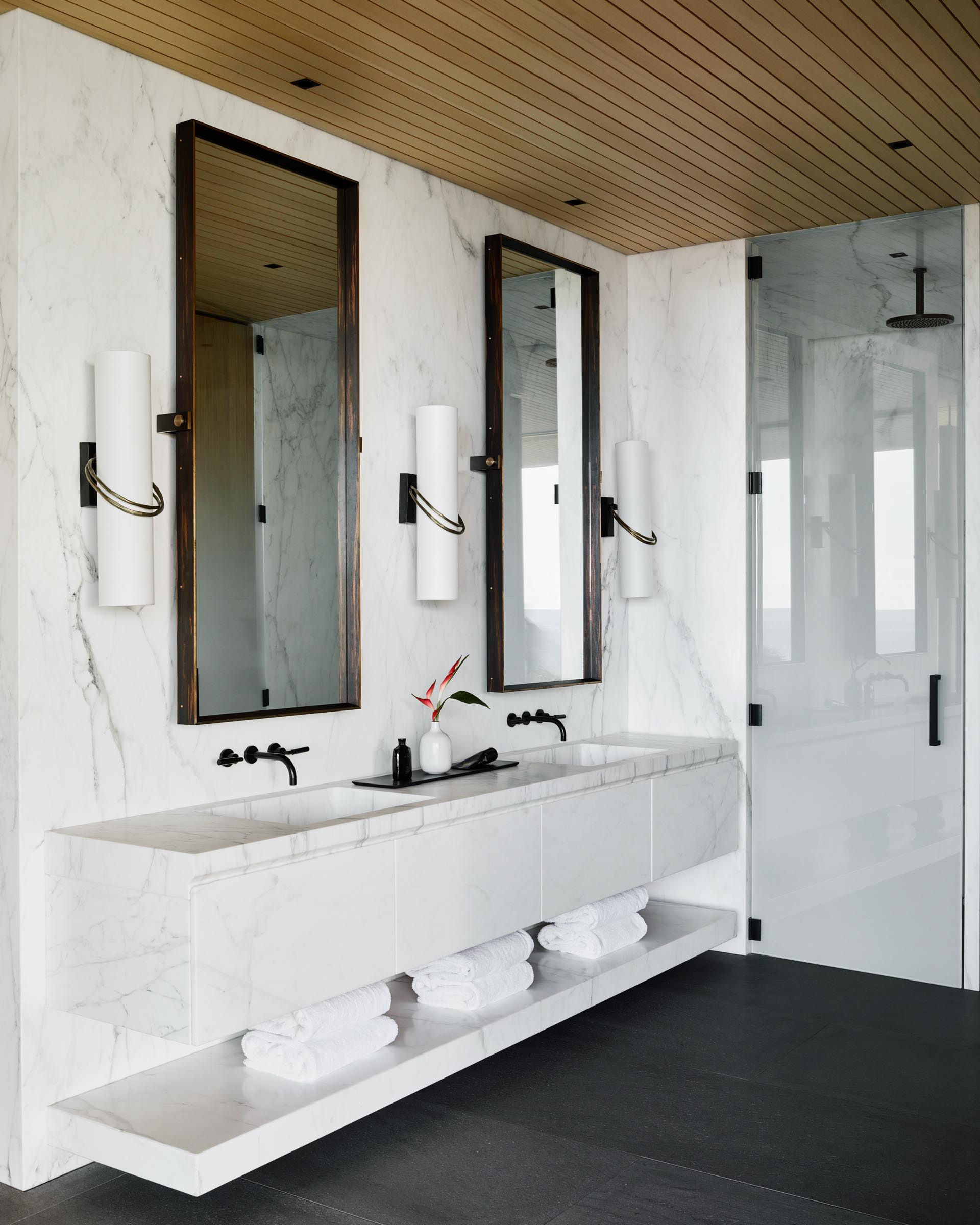 In the master bathroom, large format gray tiles cover the floor, vertical wood screens create privacy, and a white double-sink vanity floats above the ground and is adjacent to the glass-enclosed shower.
