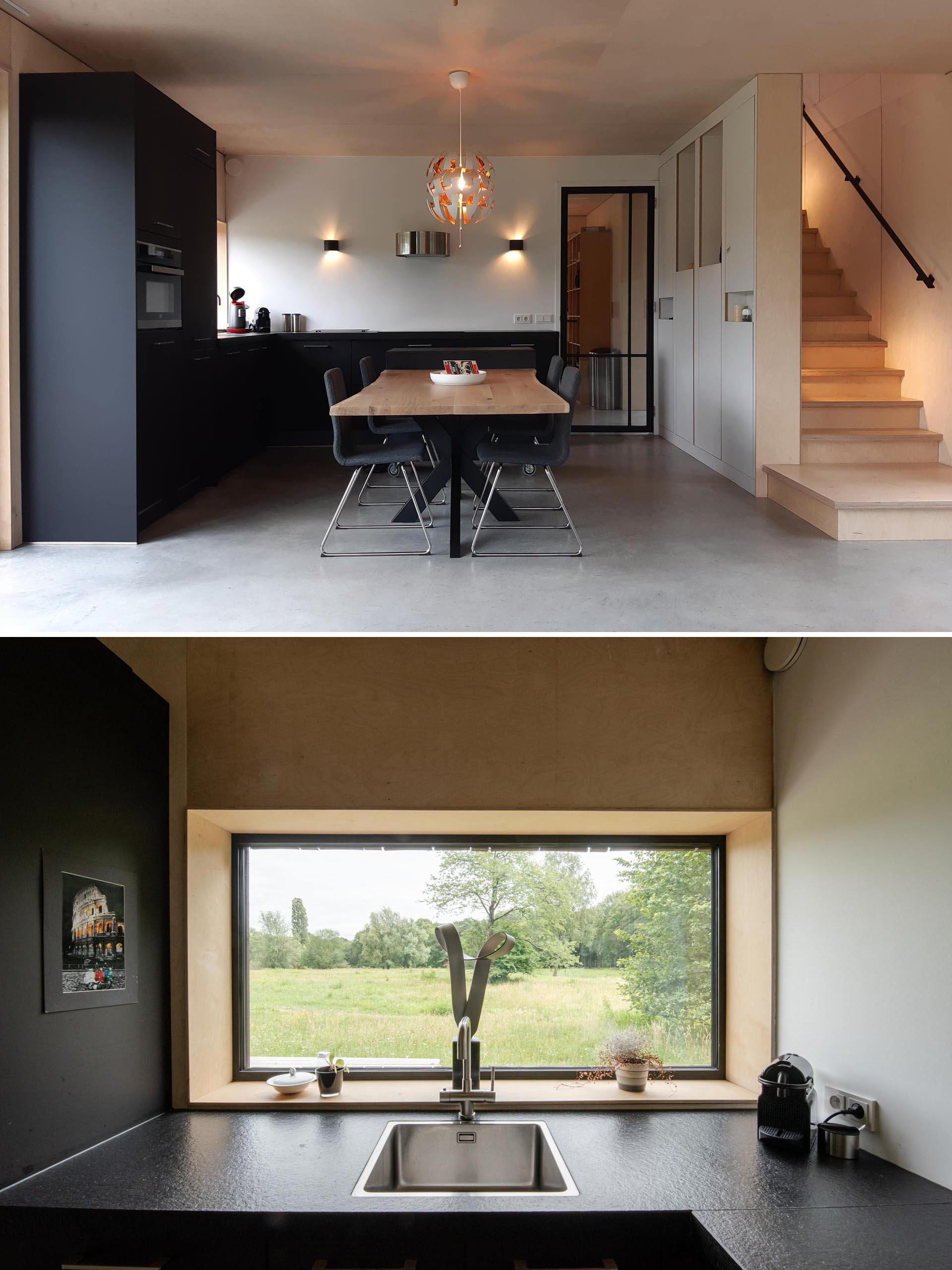A modern matte black kitchen with wood dining table.