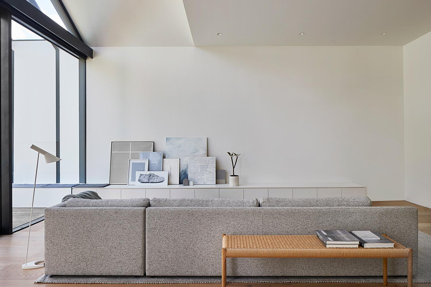 A modern living room with a neutral color palette and a low cabinet that becomes a bench outside.