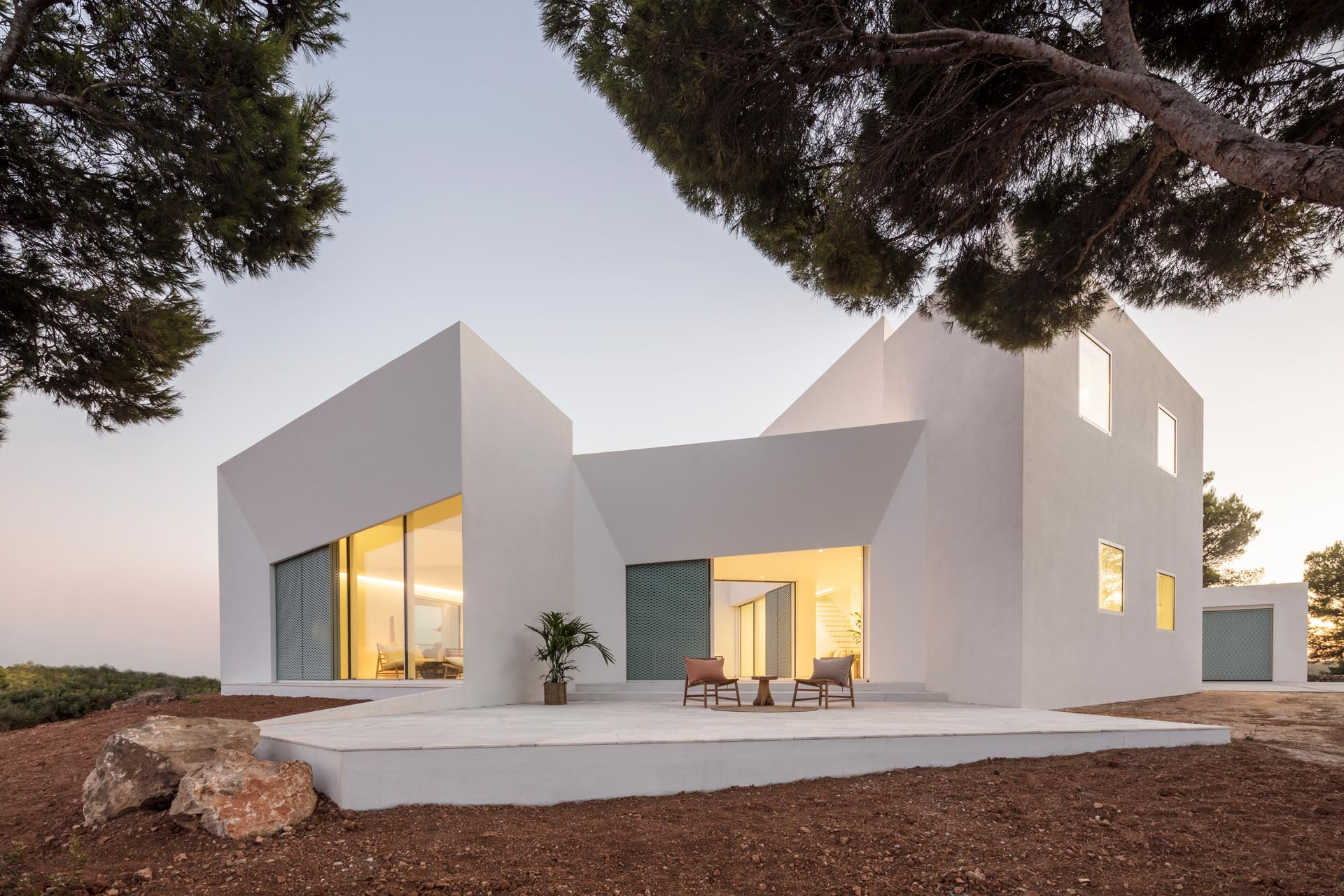 A modern white home with pastel turquoise perforated aluminum screens and an angular design.
