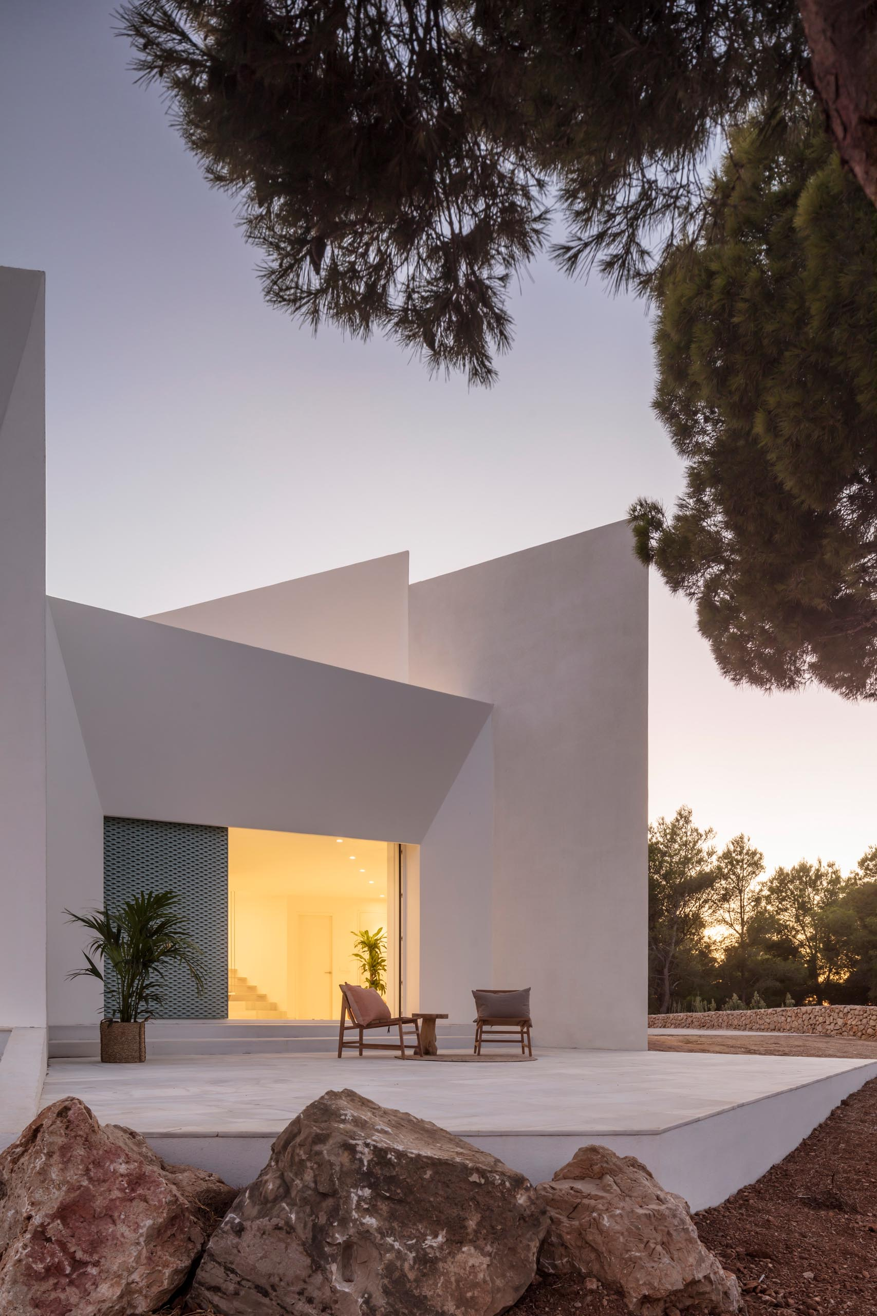 A modern white home with pastel turquoise perforated aluminum screens and multiple patios.