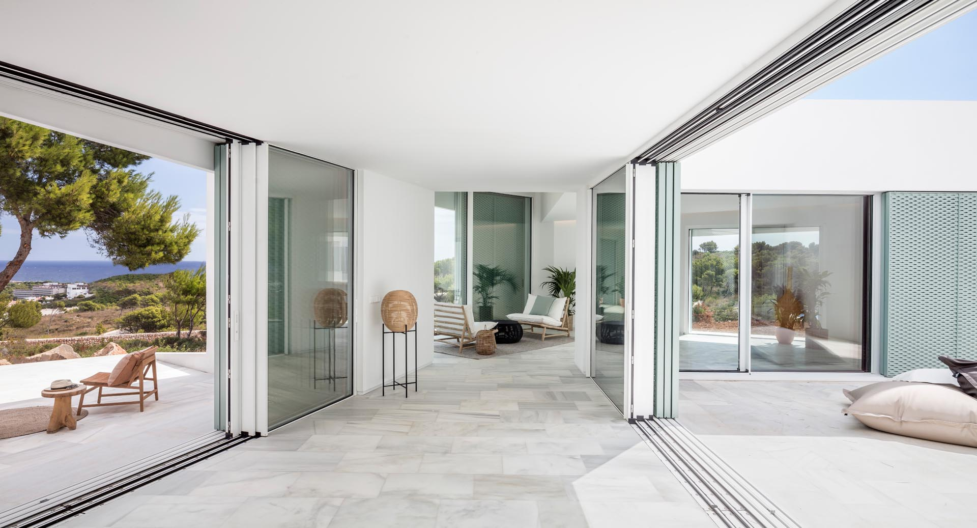 Sliding glass doors connect the interior spaces with outdoor patios.