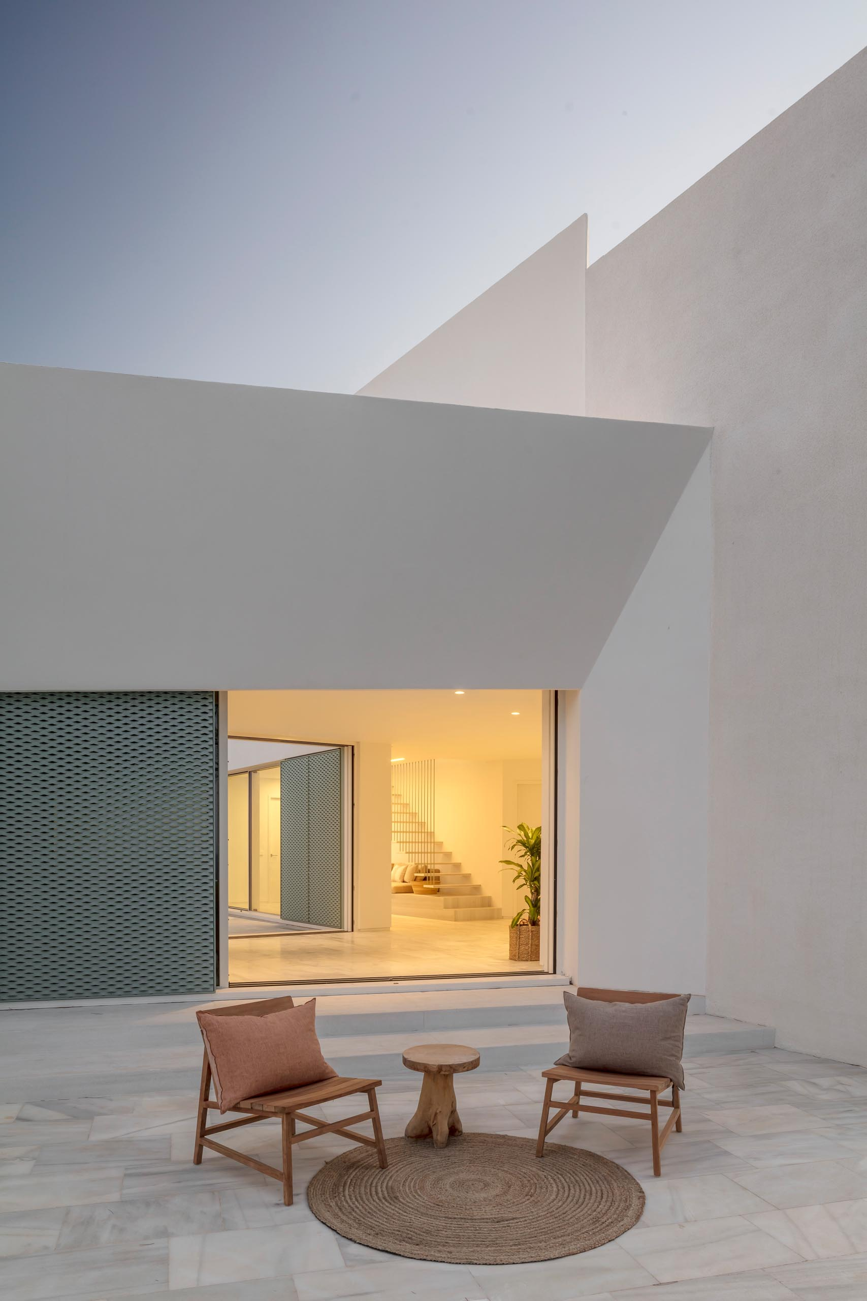 A modern white home with pastel turquoise perforated aluminum screens.