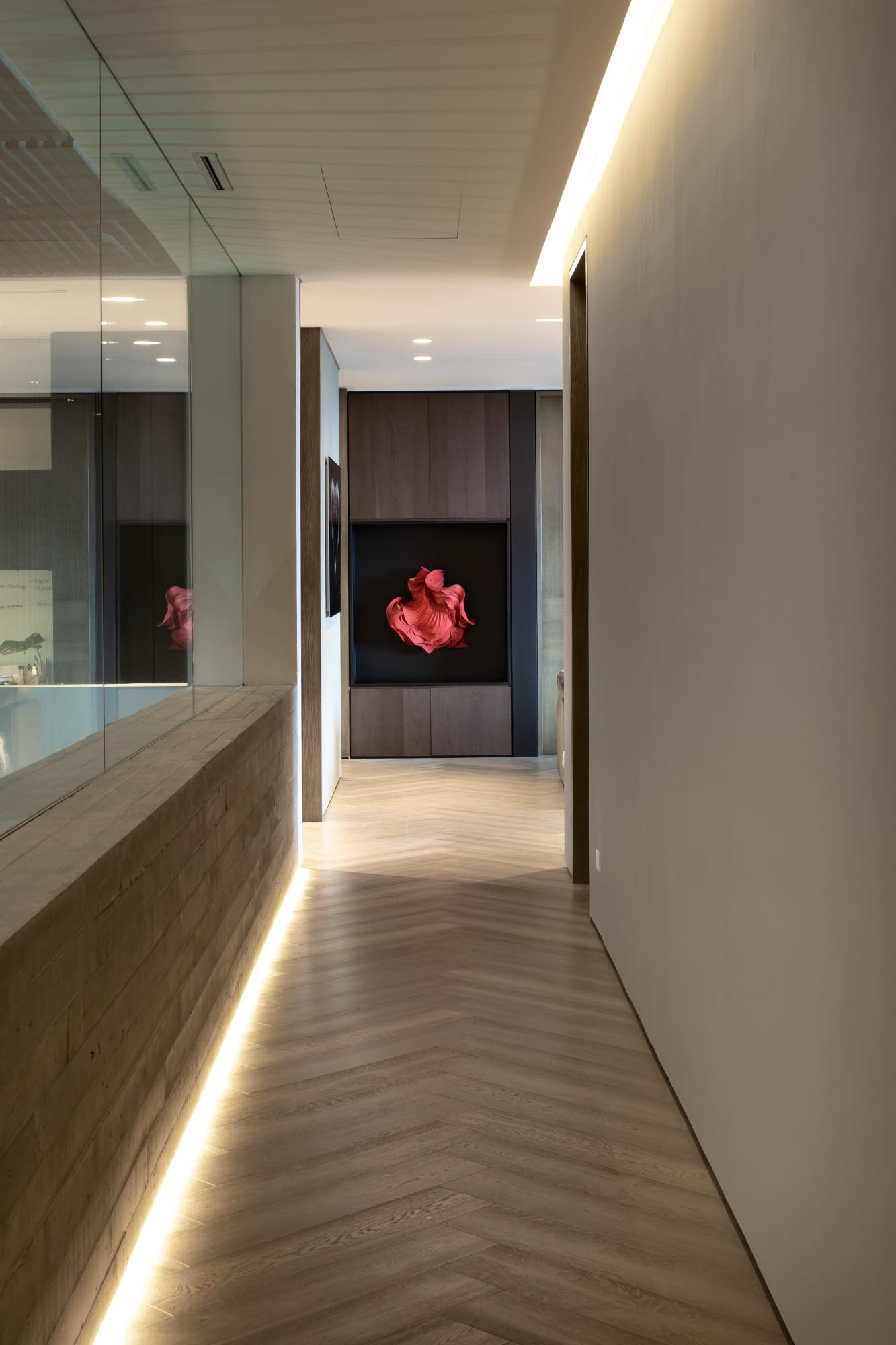 A modern hallway has a glass wall and hidden lighting incorporated into the floor and ceiling levels.