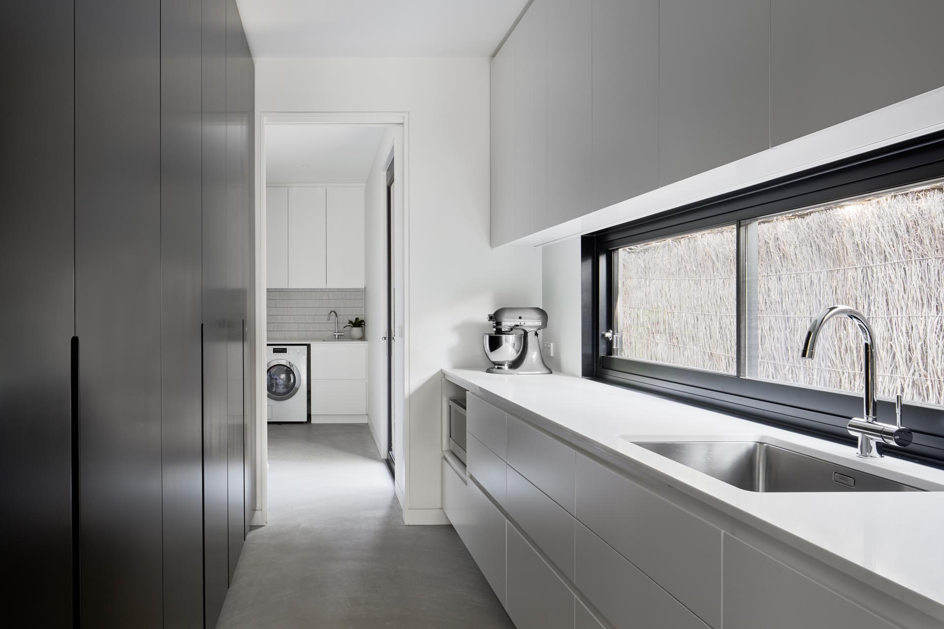 A modern pantry with black floor-to-ceiling cabinets on one wall, and white cabinetry on the other. Plus there's access to the laundry.