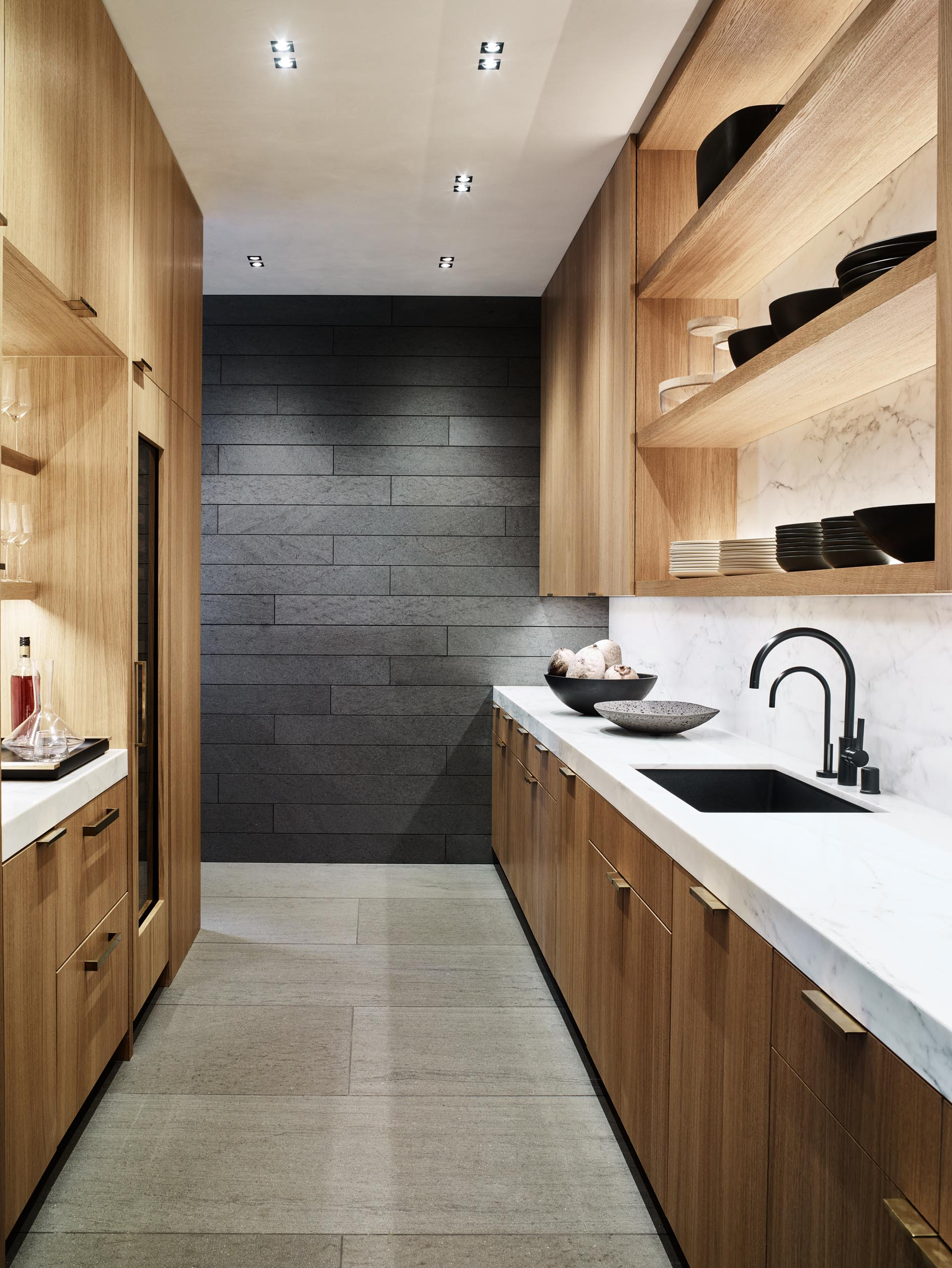 A walk-through pantry with wood cabinets and open shelving.
