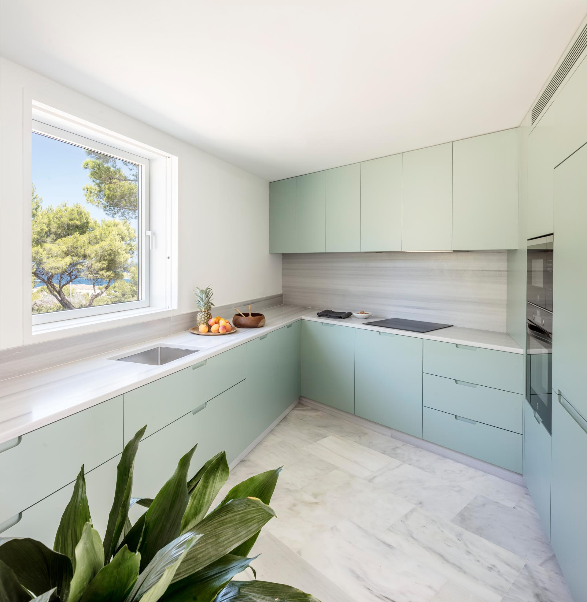 A modern kitchen with pastel green cabinets and a marble countertop and backsplash.