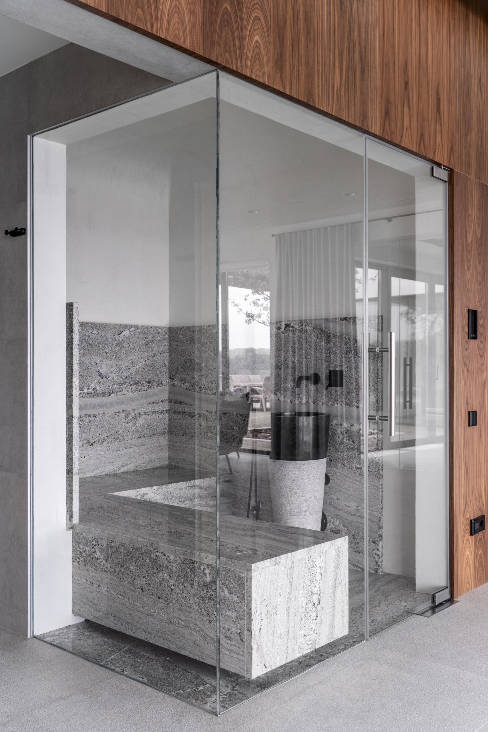 A sauna with glass walls, gray stone, and black accents.