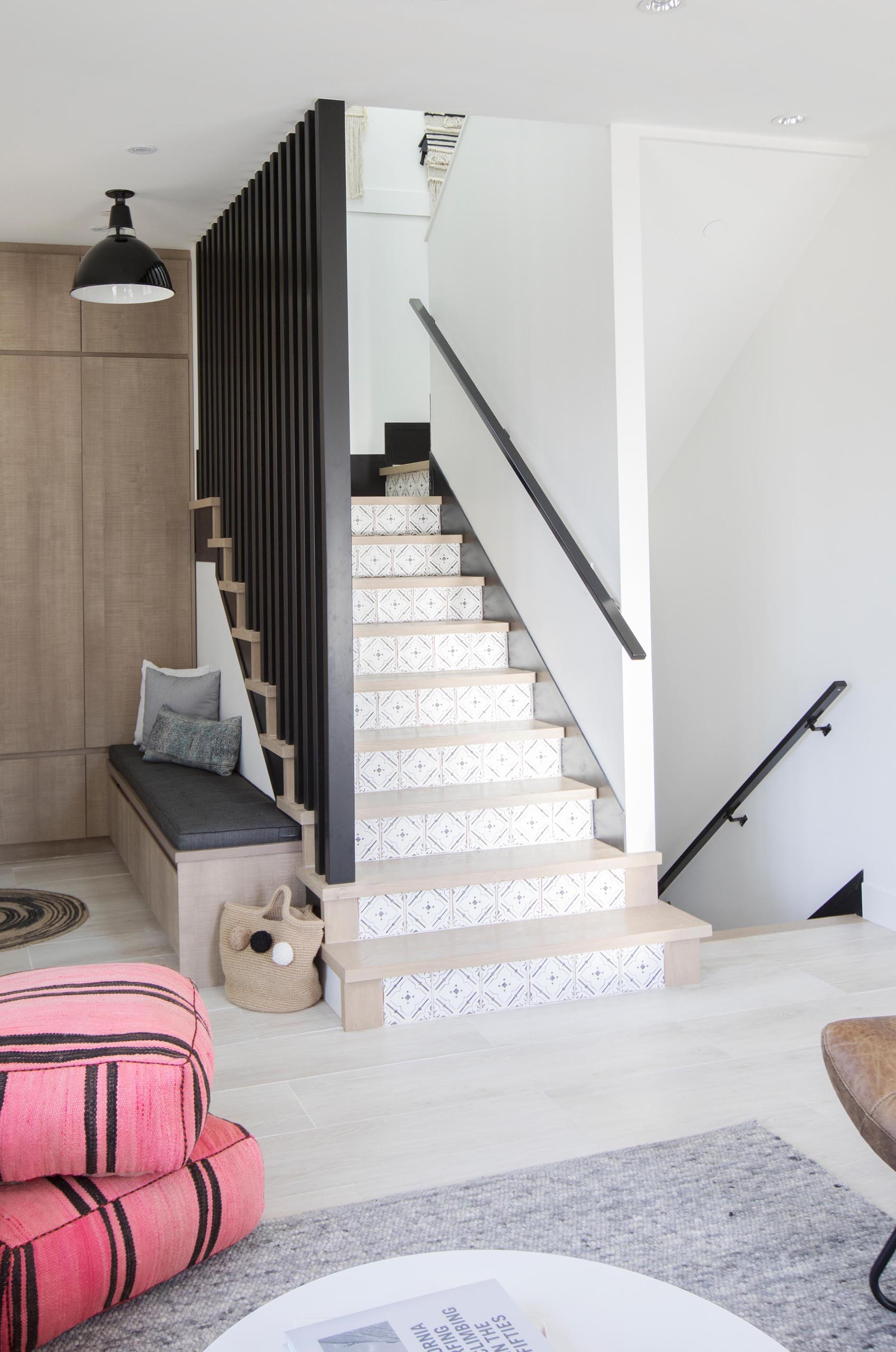 These modern stairs have a delicate pattern that's shown on the risers, while the black handrails complement other black accents throughout the home.