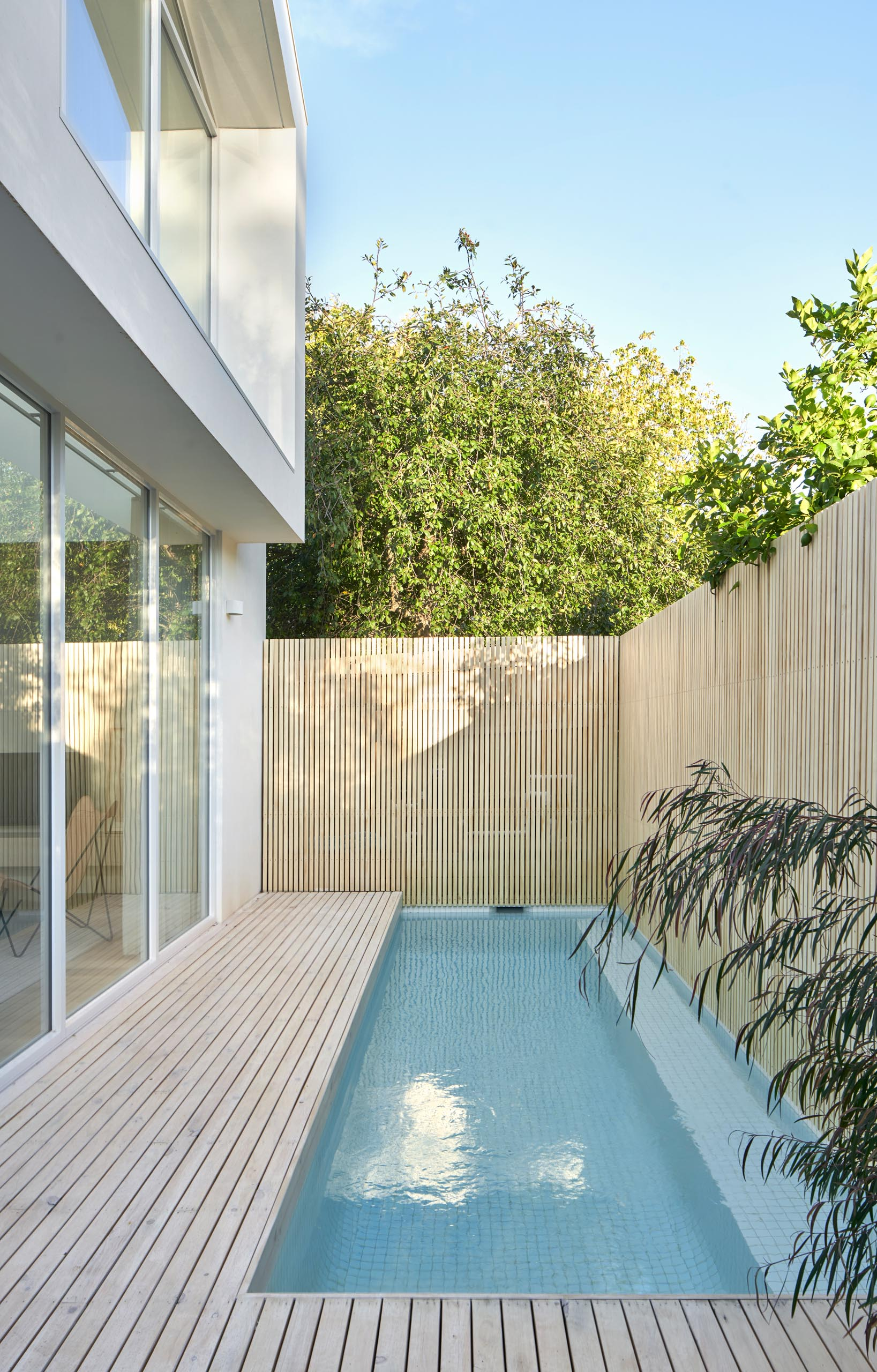 A modern house with a small plunge pool and a fence for privacy.