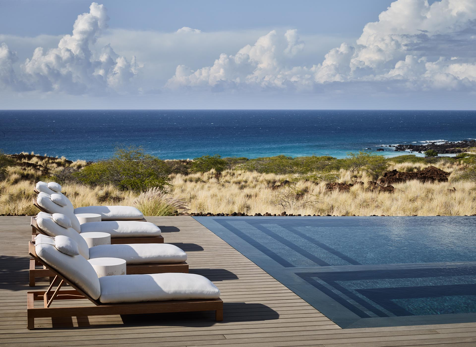 A swimming pool with a deck that overlooks the Pacific Ocean.