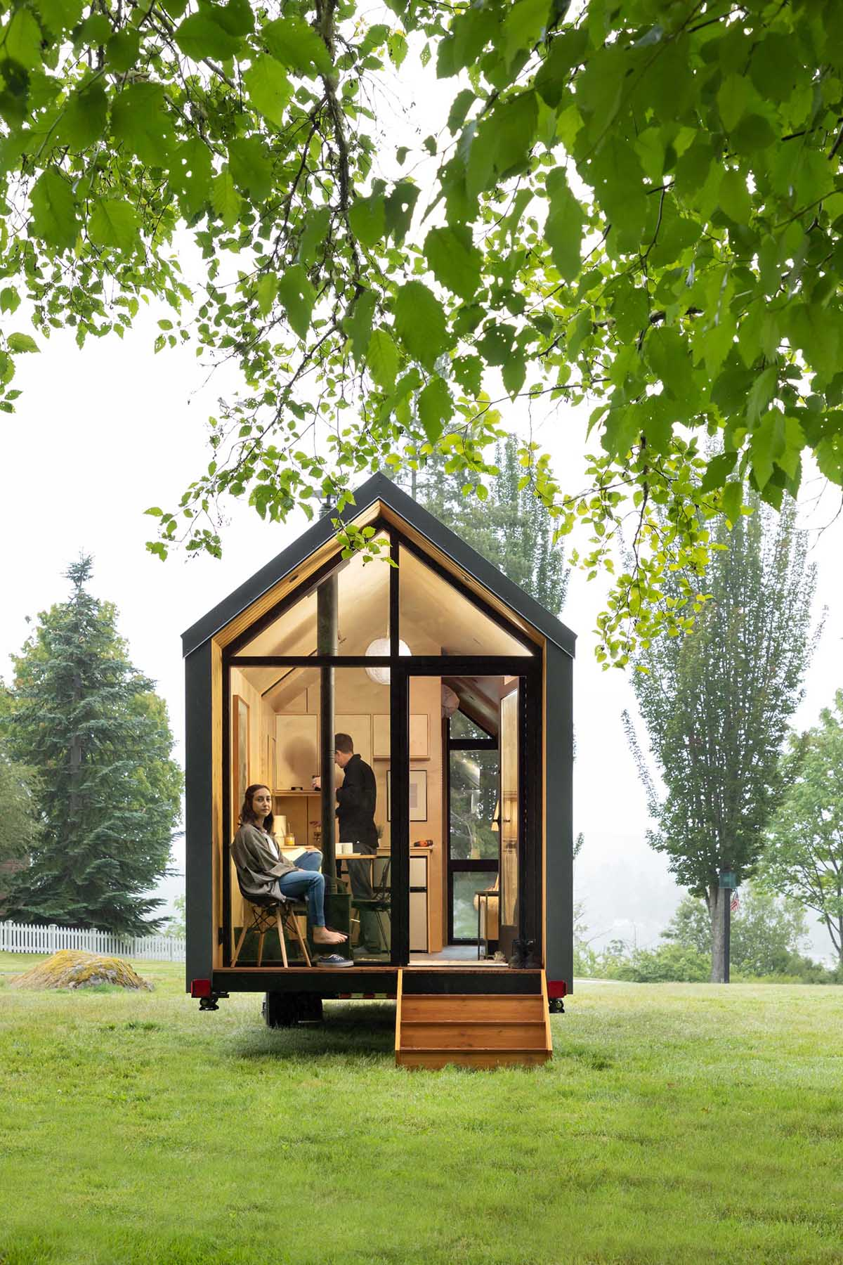 A wall of windows with a door at one end of this modern tiny home allows for natural light to filter through, and creates a connection to the small porch and the outdoors.