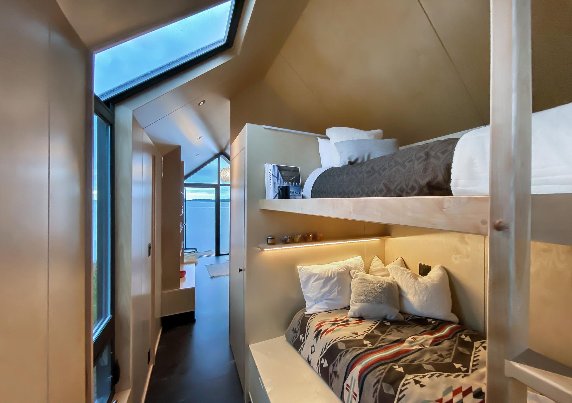A tiny house with bunk beds that don't feel enclosed due to the gabled ceiling.