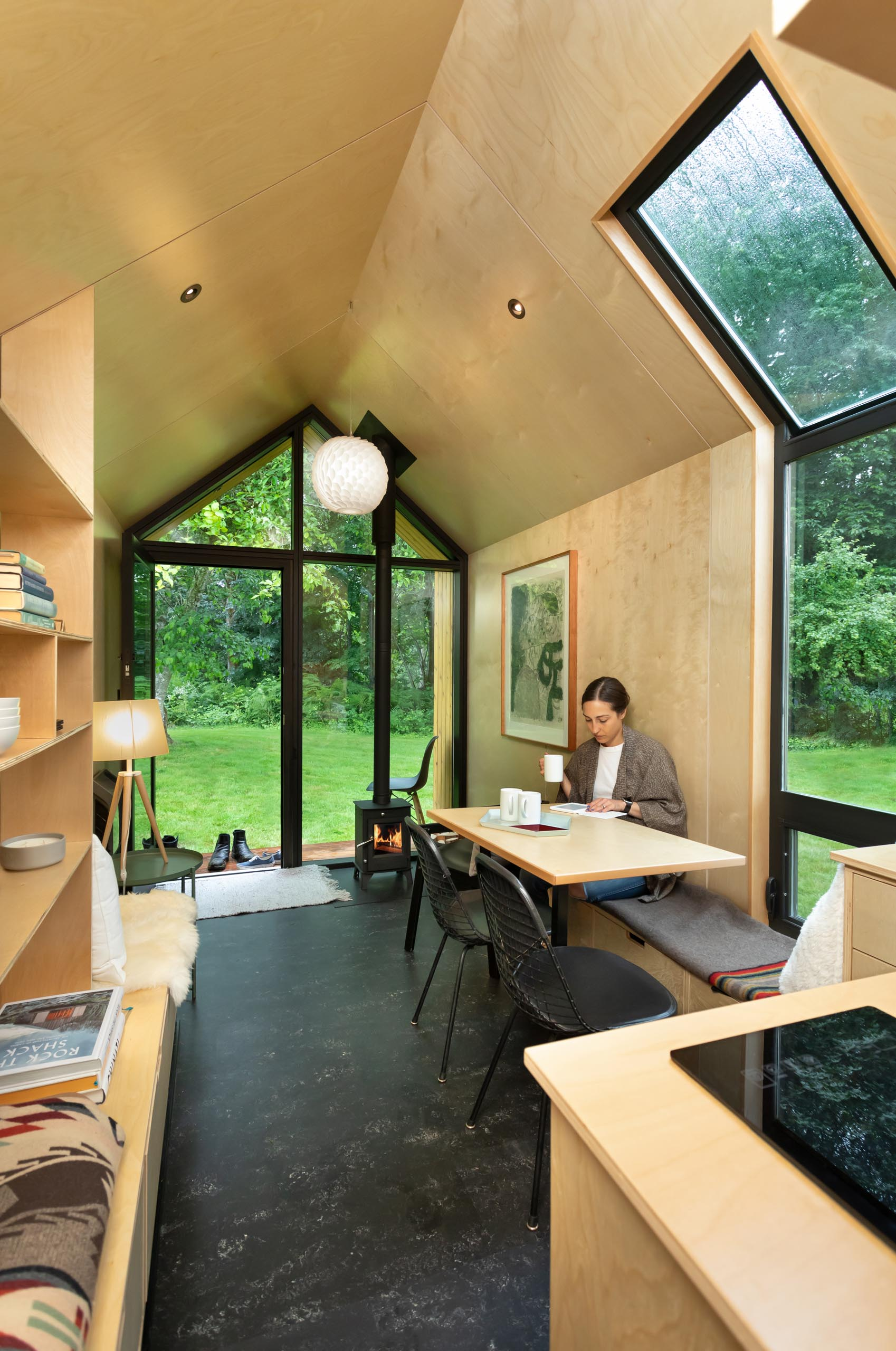 A modern tiny home with built-in benches, a wood burning stove, matte black linoleum flooring, and a small porch.