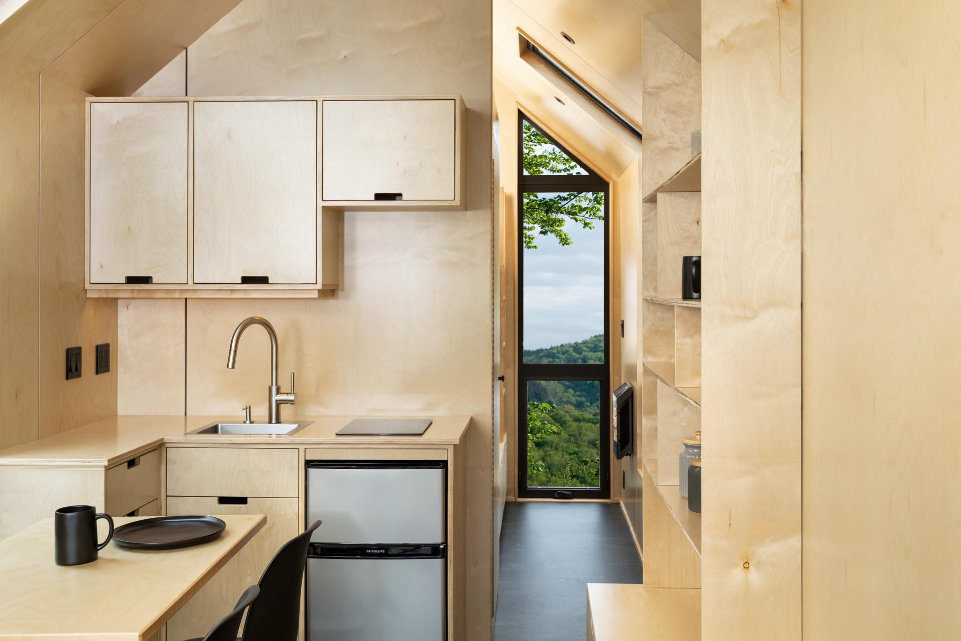 Pre-finished birch-faced plywood has been used in the kitchen of this tiny home to create the hardware free, soft close cabinets. There's also an electric refrigerator and induction single-burner cooktop.