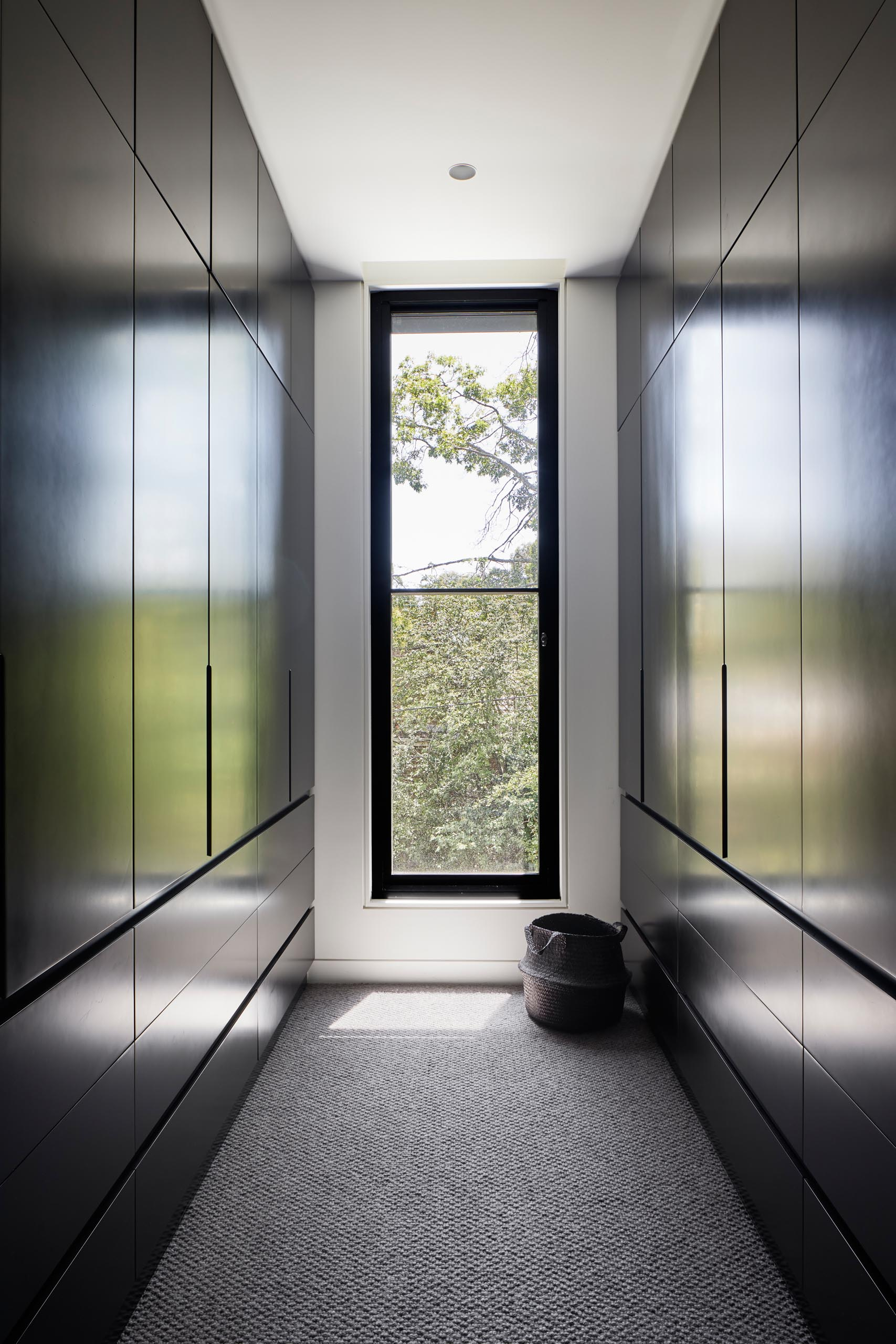 In this modern walk-in closet, there's dark floor-to-ceiling cabinetry that lines the walls, and allows the eye to focus on the tree view through the window.