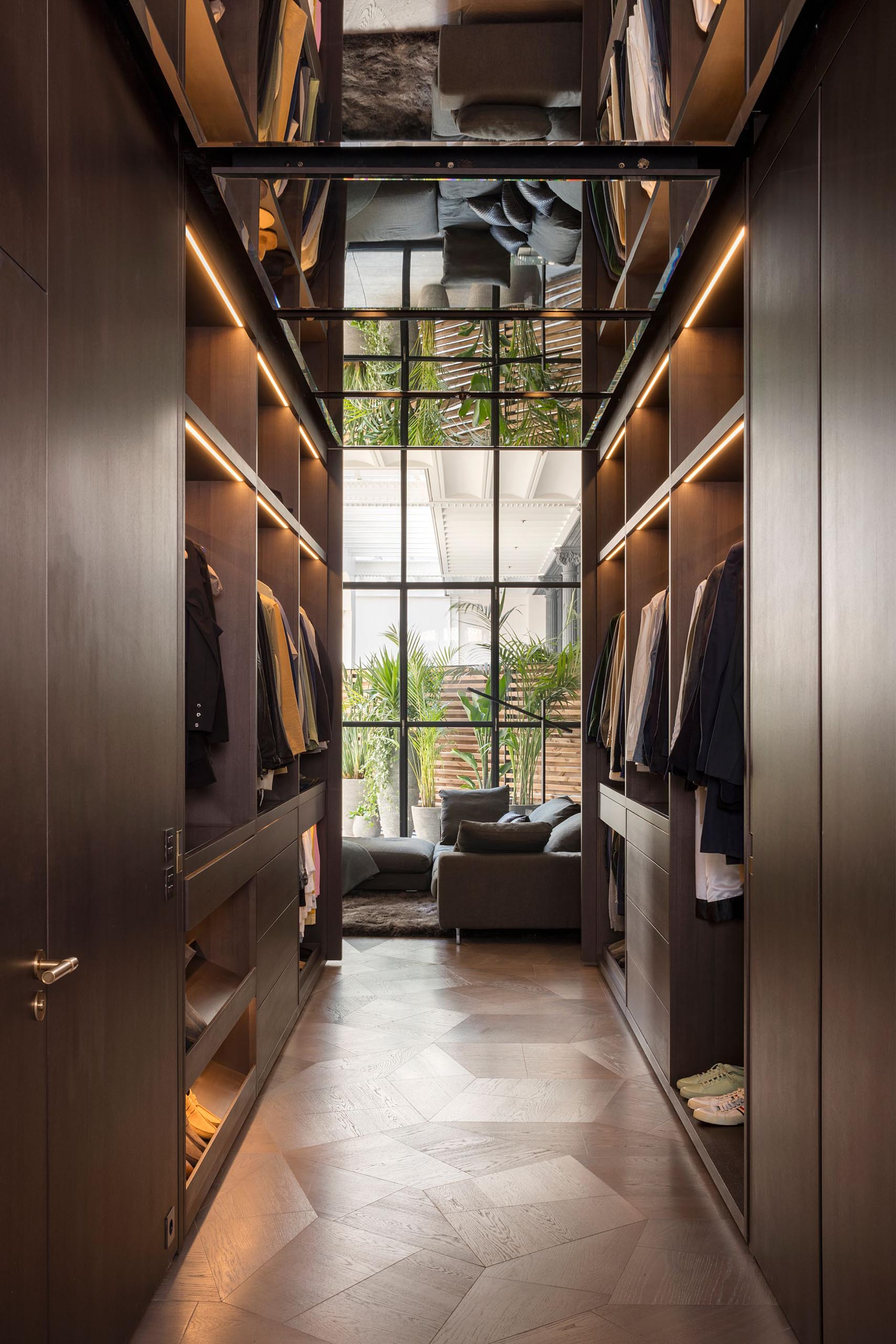 A walk-through closet with plenty of hanging space highlighted by LED strips.
