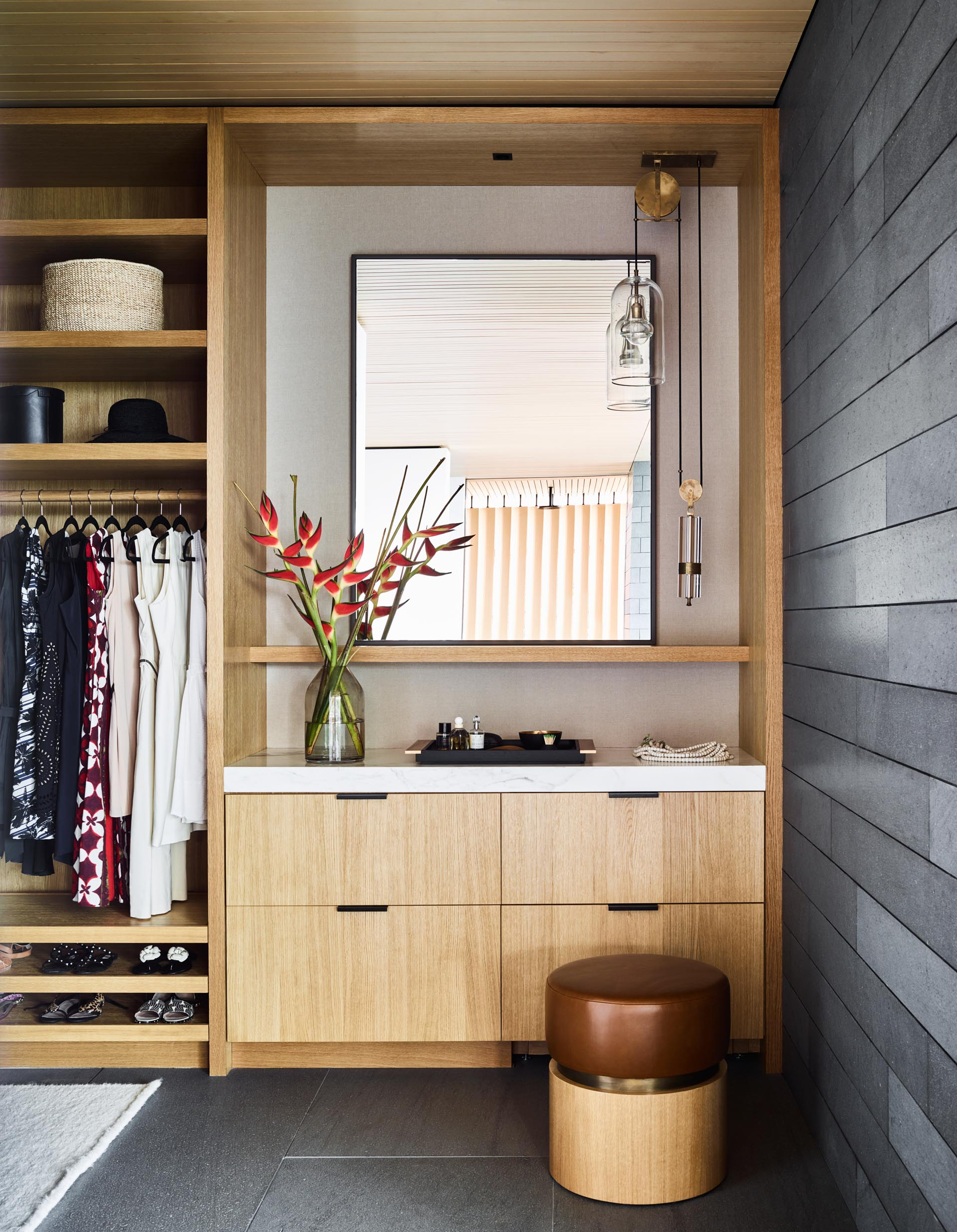 A modern walk-in closet with a vanity area, drawers, shelving, and space for hanging clothes.