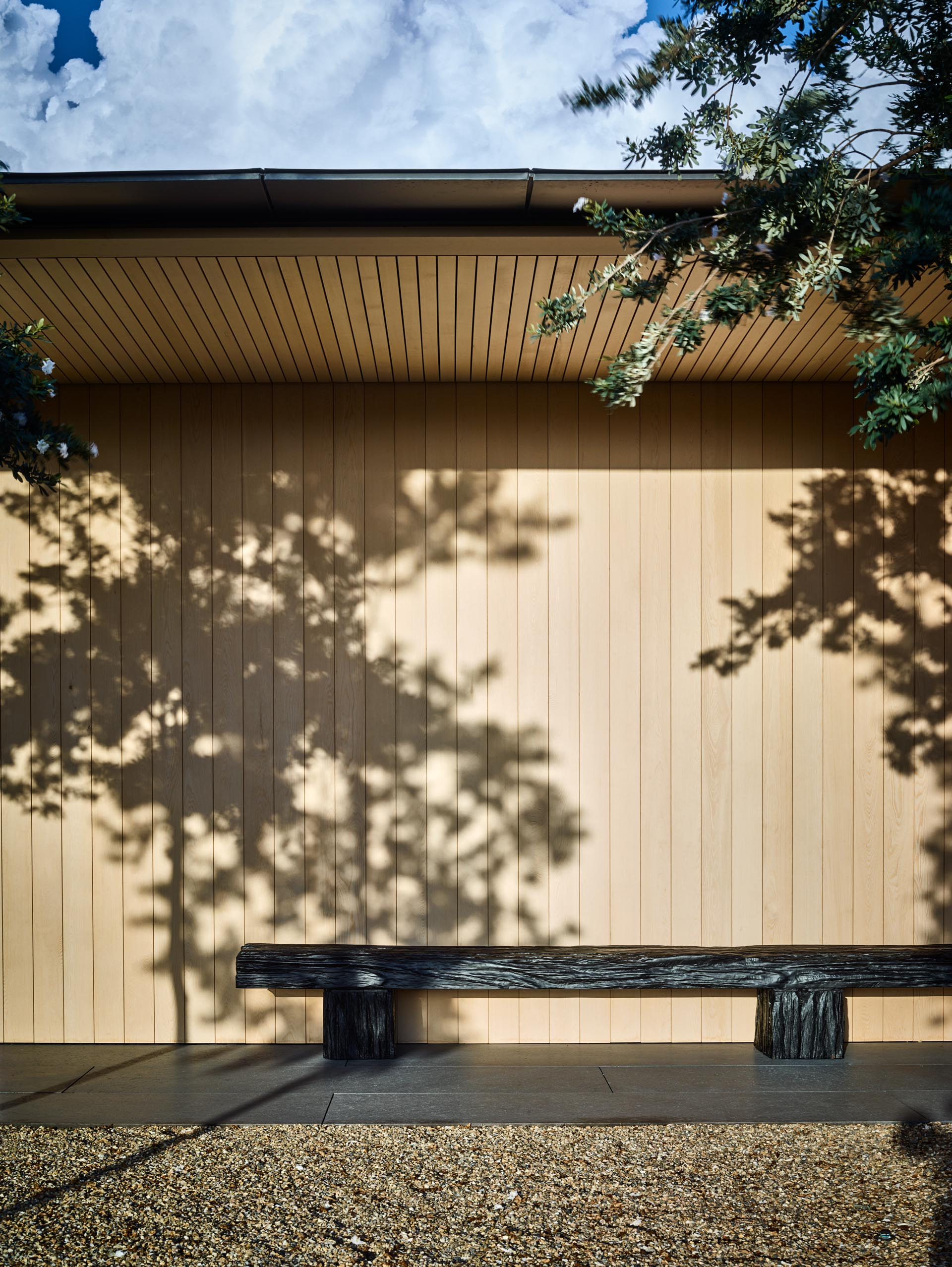 A modern home with light wood siding and a covered pathway.