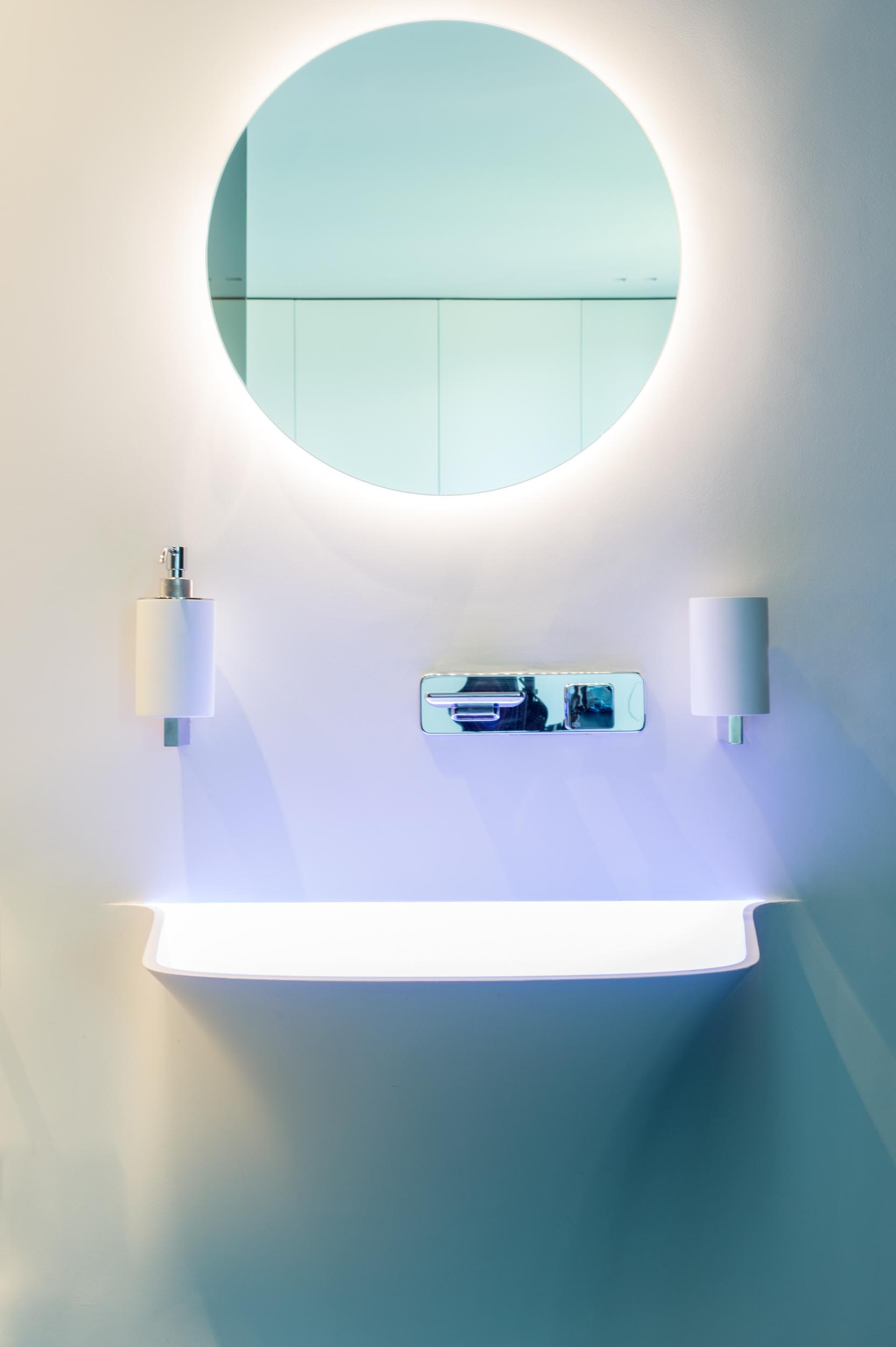 A modern bathroom with a seamless  white vanity and backlit round mirror.