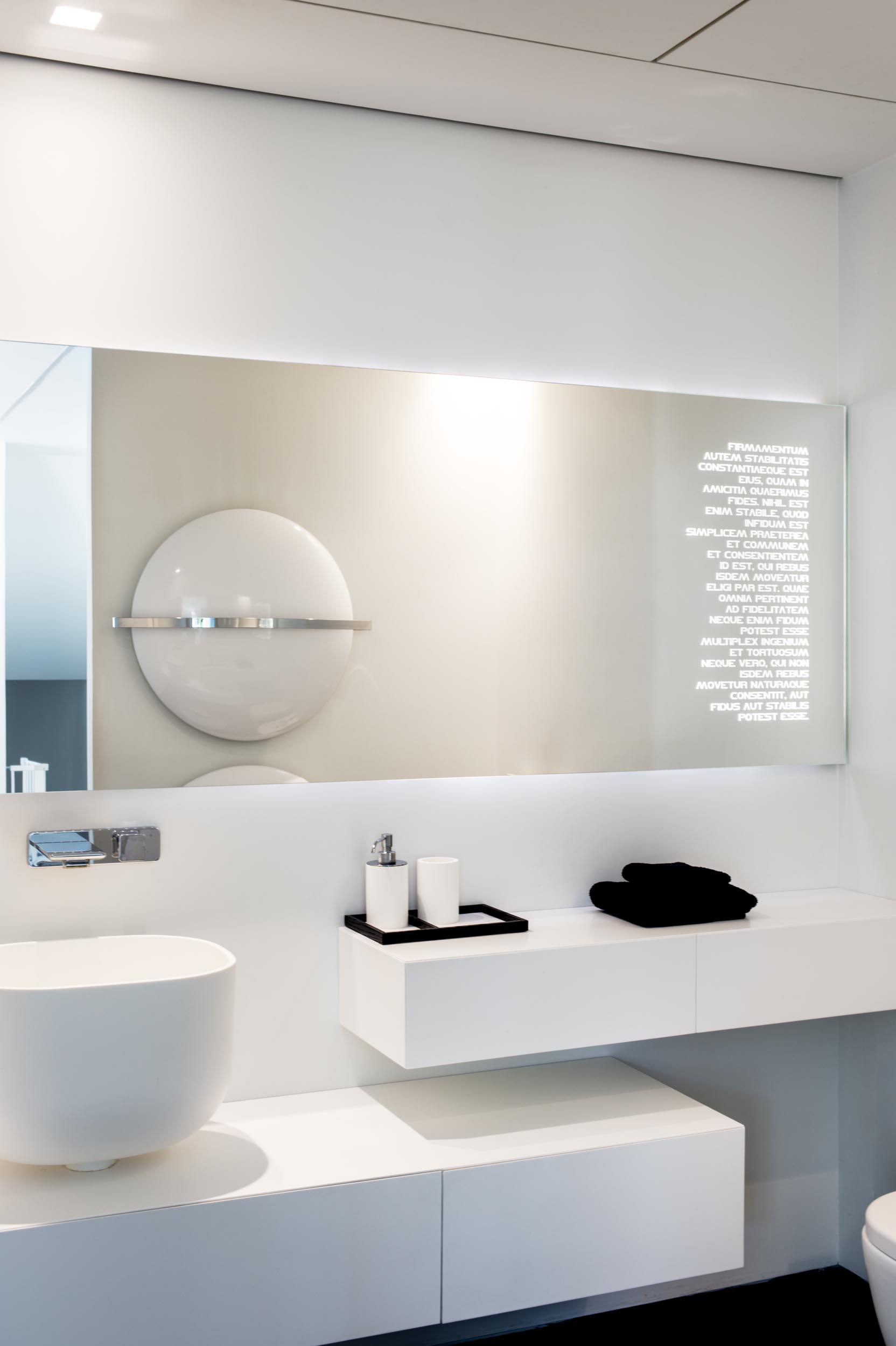 A modern bathroom white a white vanity and backlit mirror.
