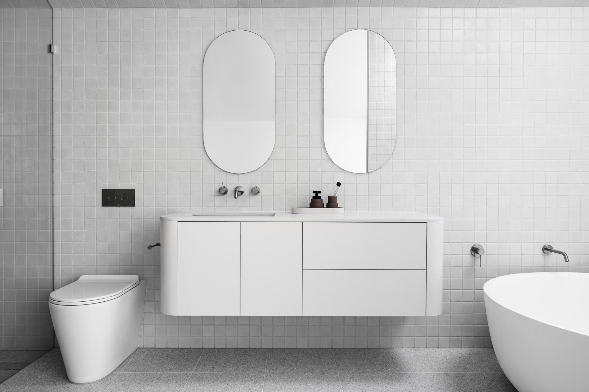In this modern bathroom, square gray tiles cover the walls and floor, while pill-shaped mirrors hang above the floating white vanity with curved corners. One end of the bathroom is dedicated to the shower, while the other has a round freestanding bathtub located beneath a skylight.