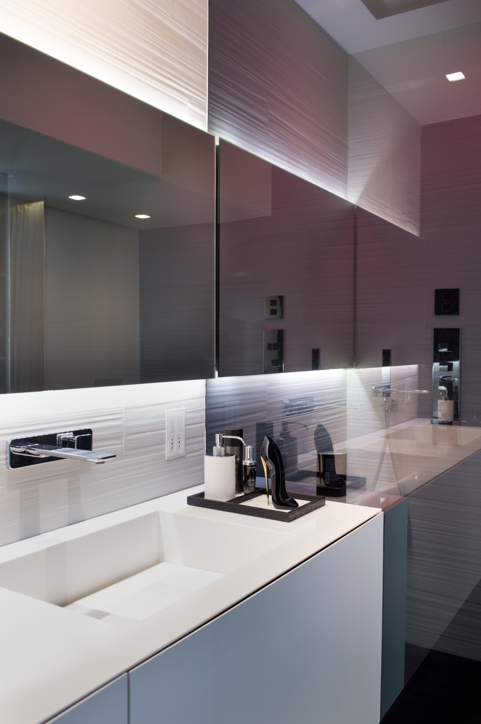 A modern bathroom with a white vanity and backlit mirror.