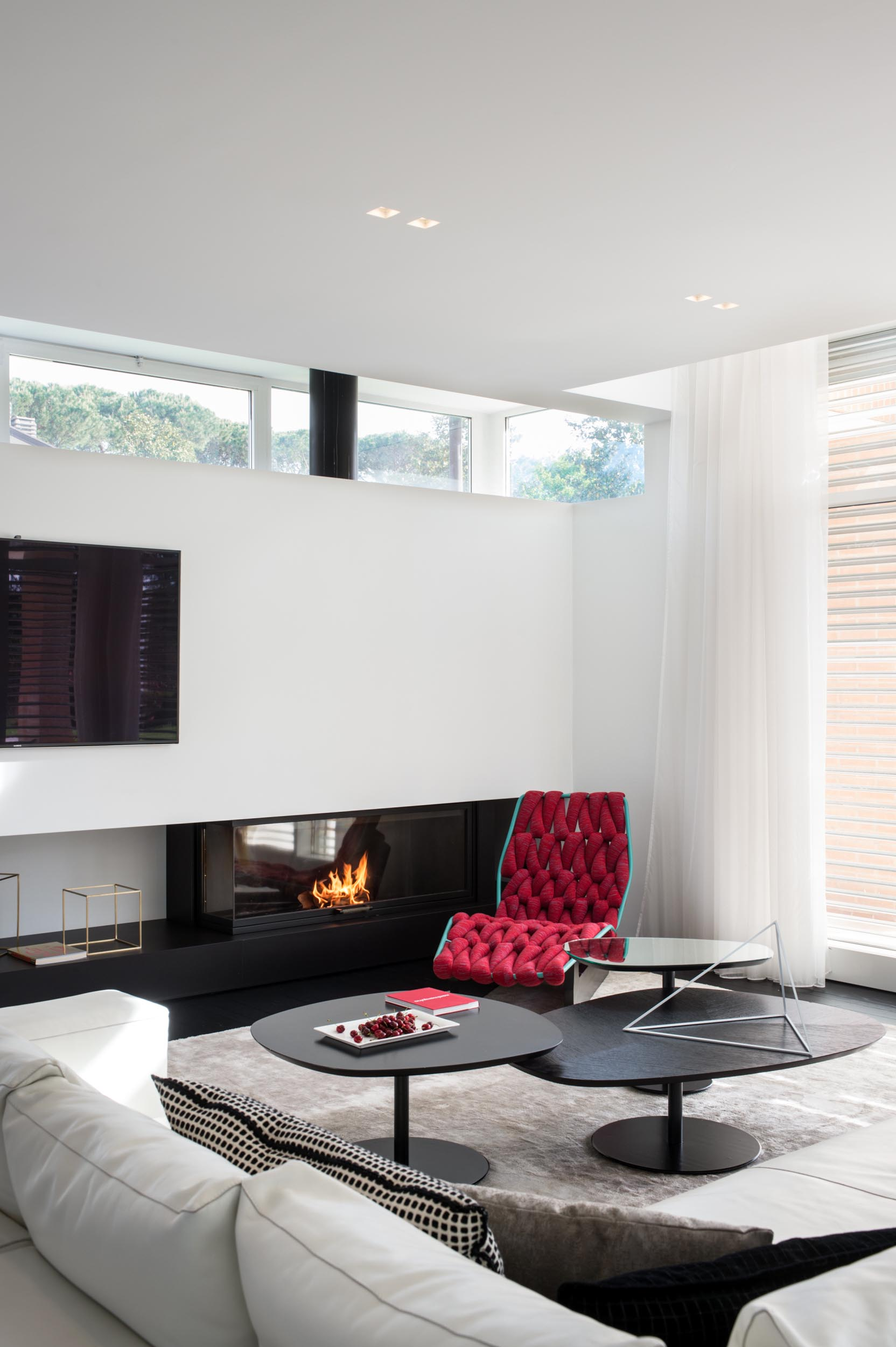 In this modern living room, a white corner sofa sits on top of a large rug, while black coffee tables complement the black fireplace. A woven red chaise has been chosen to add a touch of color.