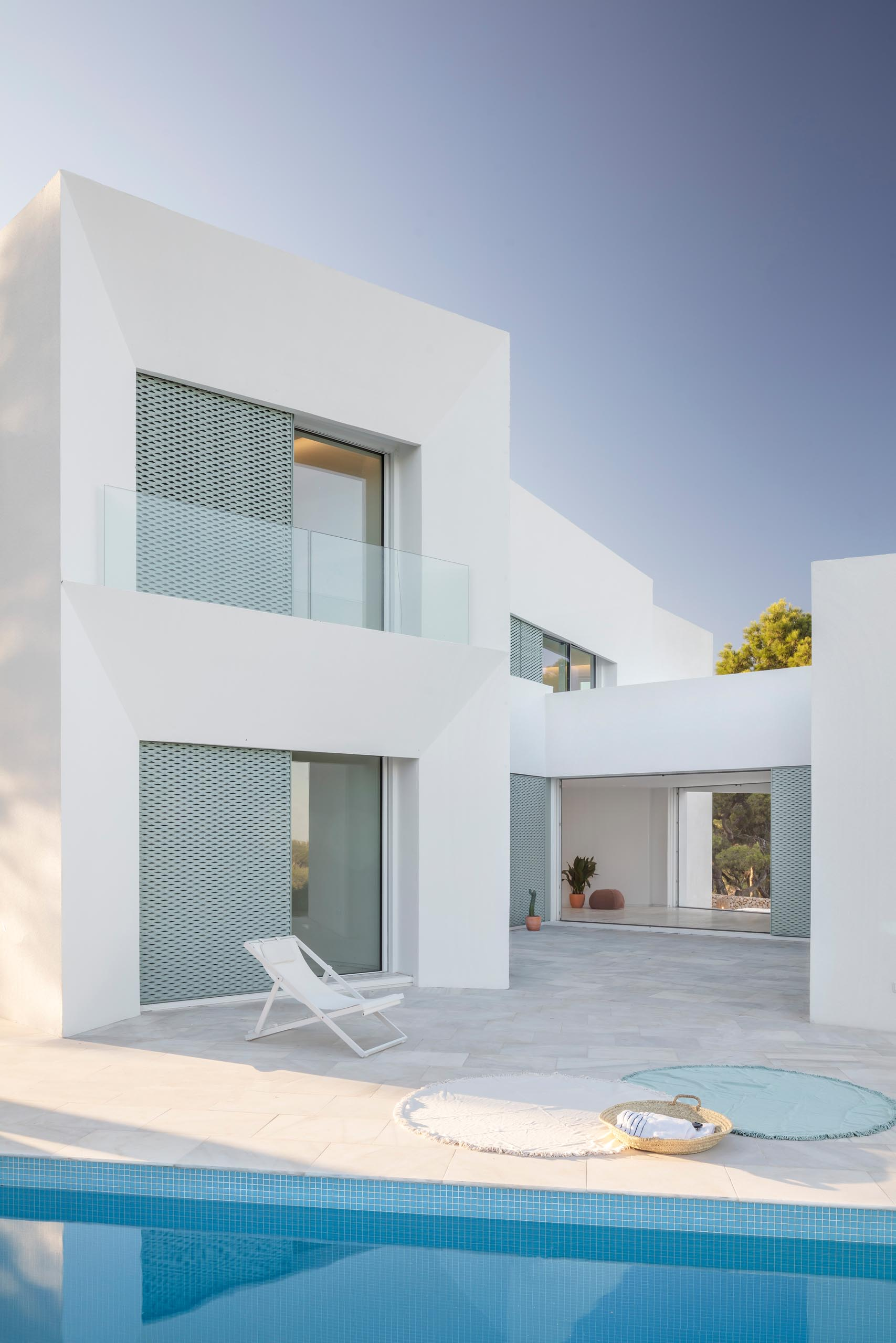 A modern white home with pastel turquoise perforated aluminum screens, a patio, and swimming pool.