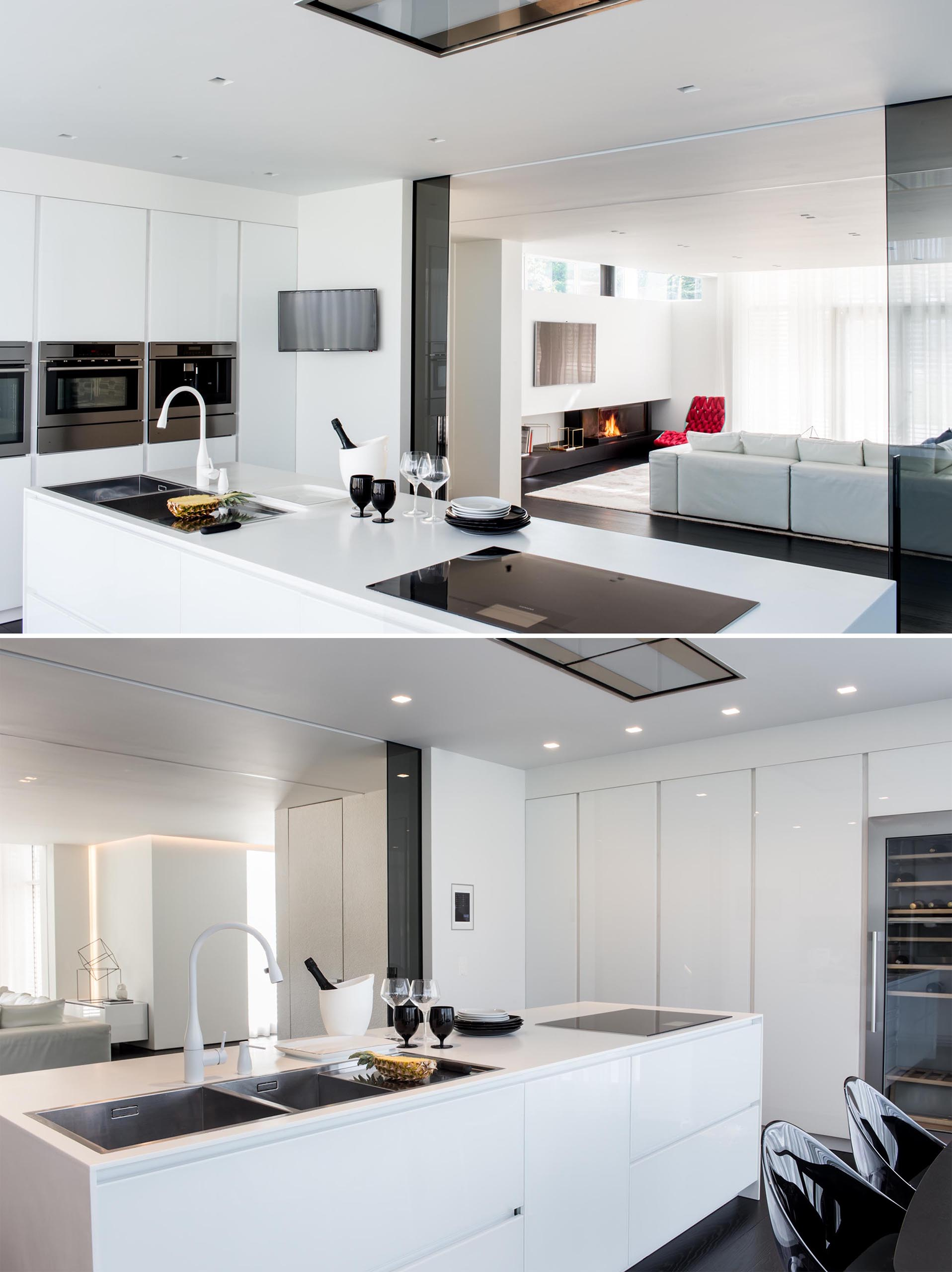A modern kitchen with minimalist white cabinets, stainless steel appliances, and an island.