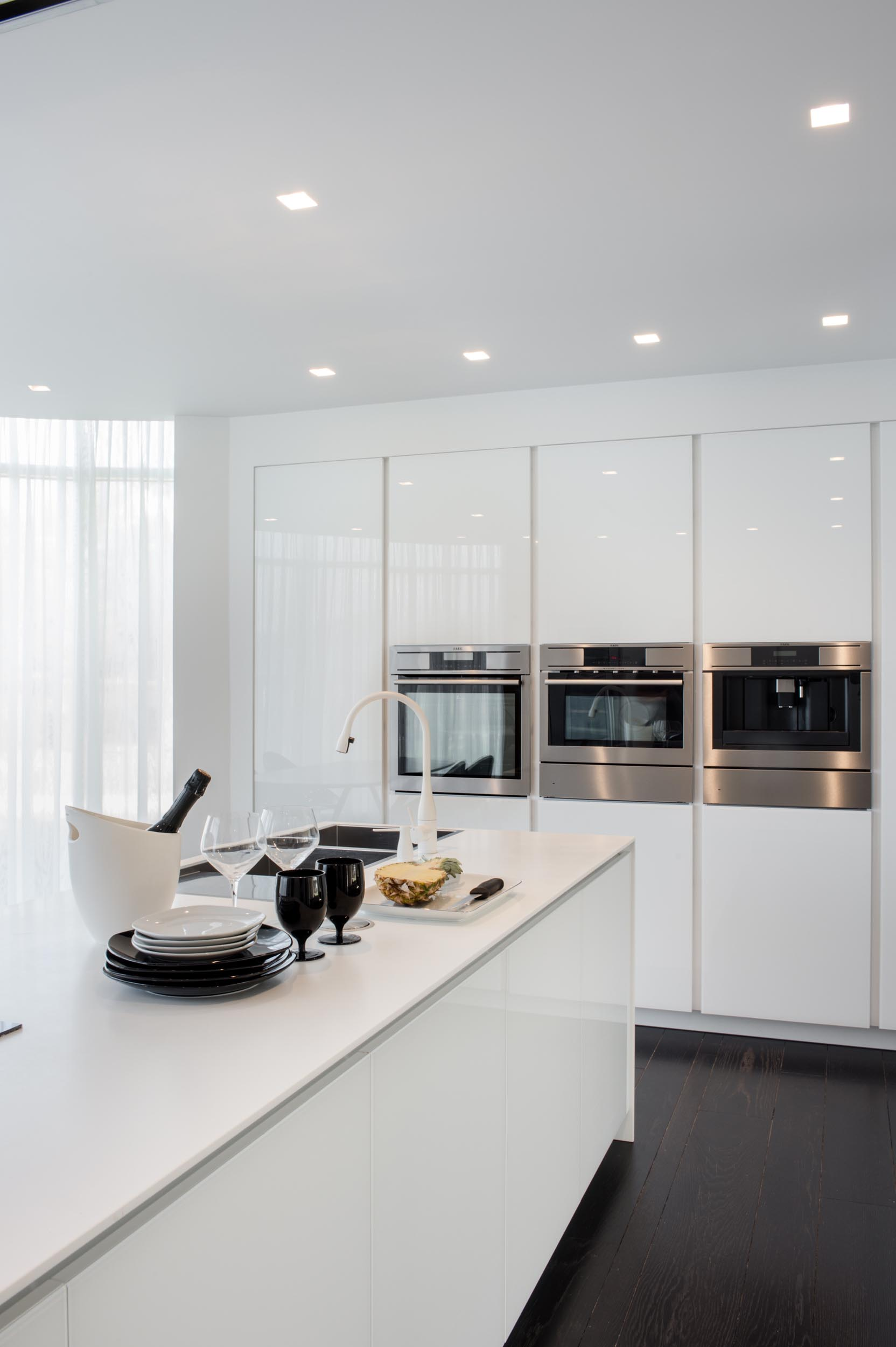 A modern kitchen with minimalist white cabinets and an island.