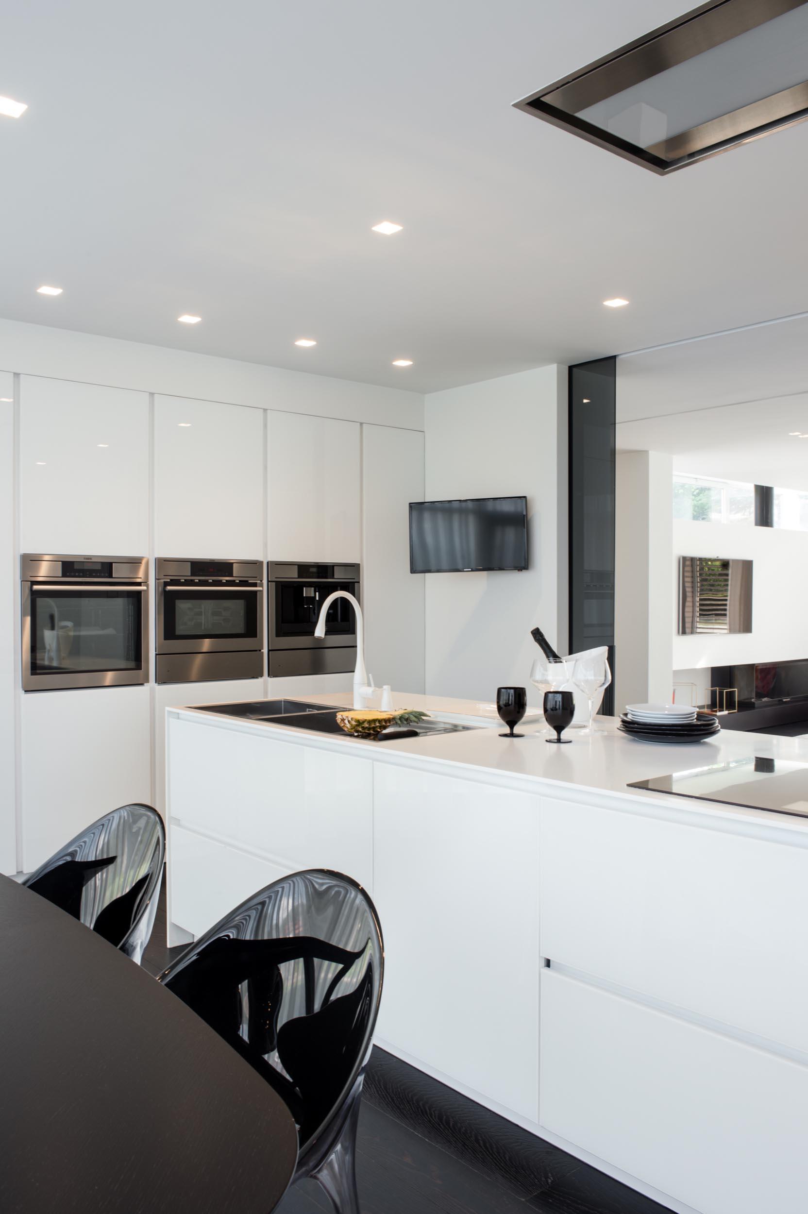 A modern kitchen with minimalist white cabinets.