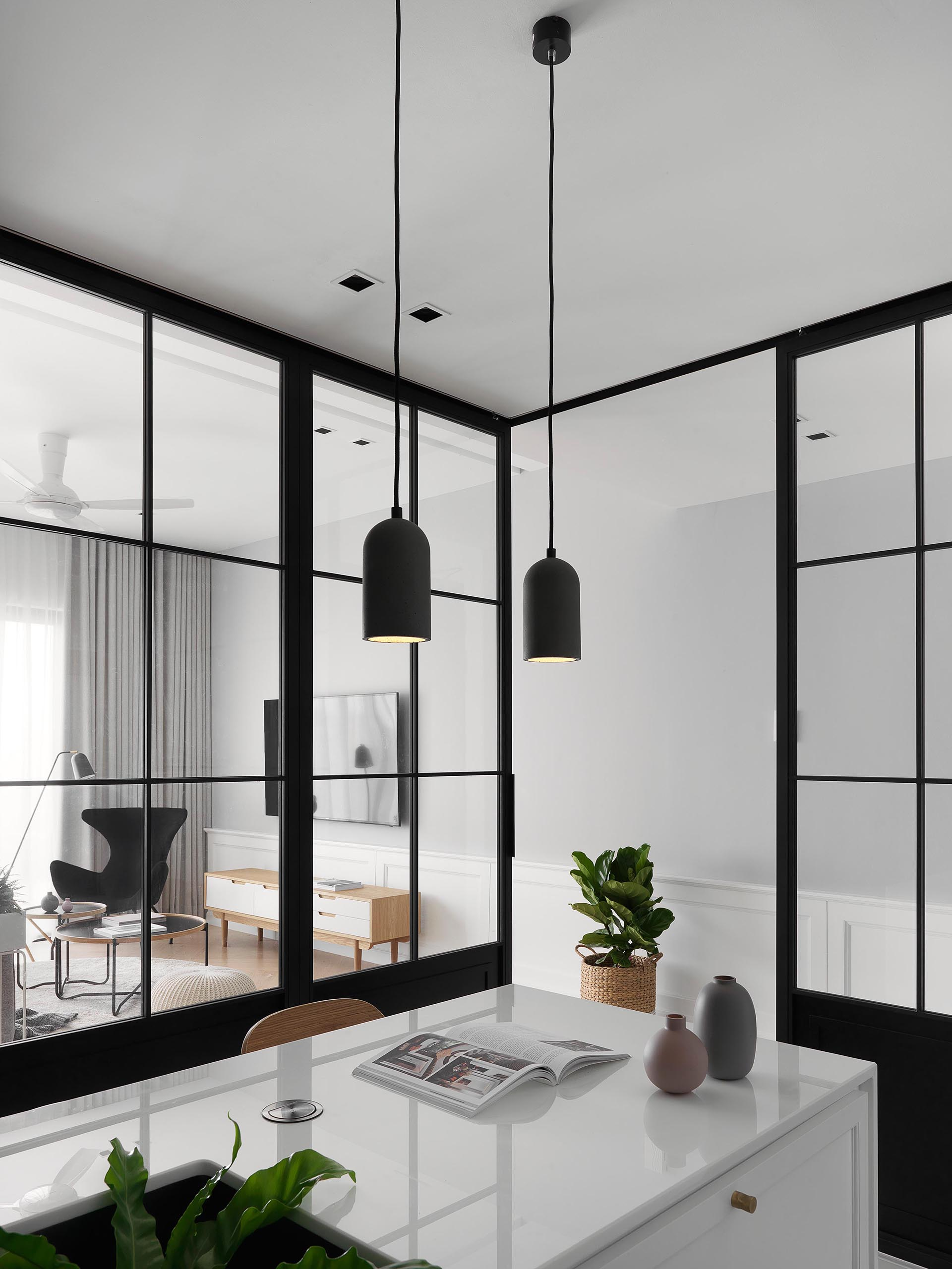 Sliding black-framed glass doors separate this modern kitchen from the living room and dining room.