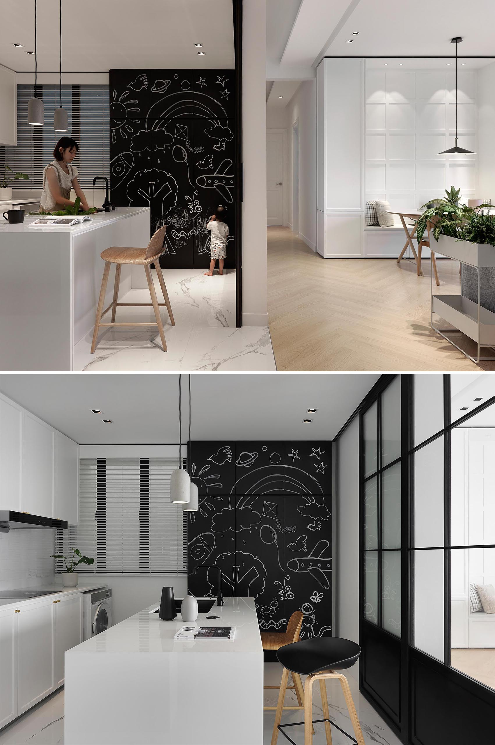 This minimalist kitchen features white cabinets and a white island, as well as a contrasting section of cabinets with chalkboard fronts.