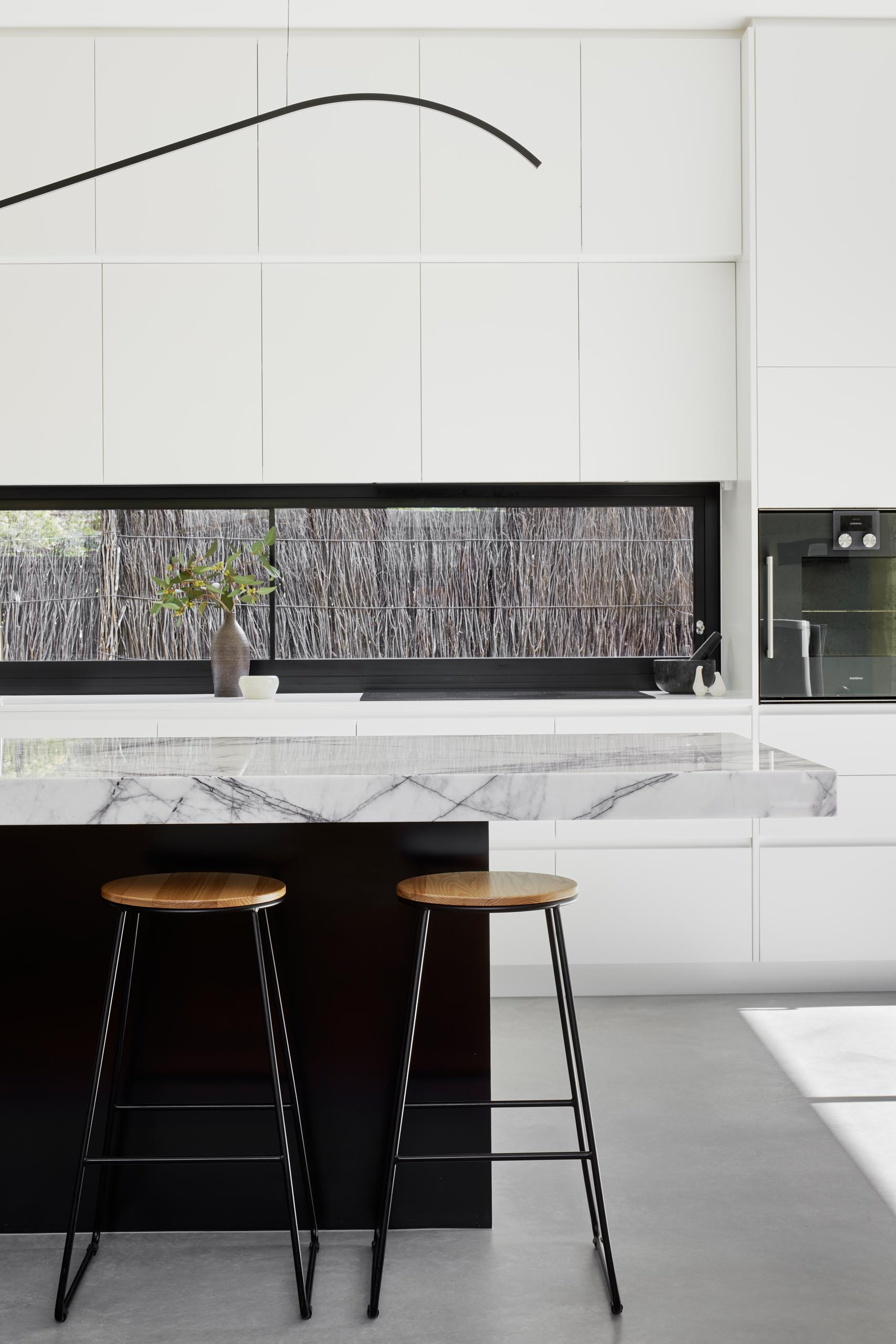 In this modern kitchen, minimalist white cabinets with an integrated fridge and freezer, contrast the built-in appliances, horizontal black window frame, and the black island base. The island has a thick marble countertop, while pure white countertops are featured along the wall.