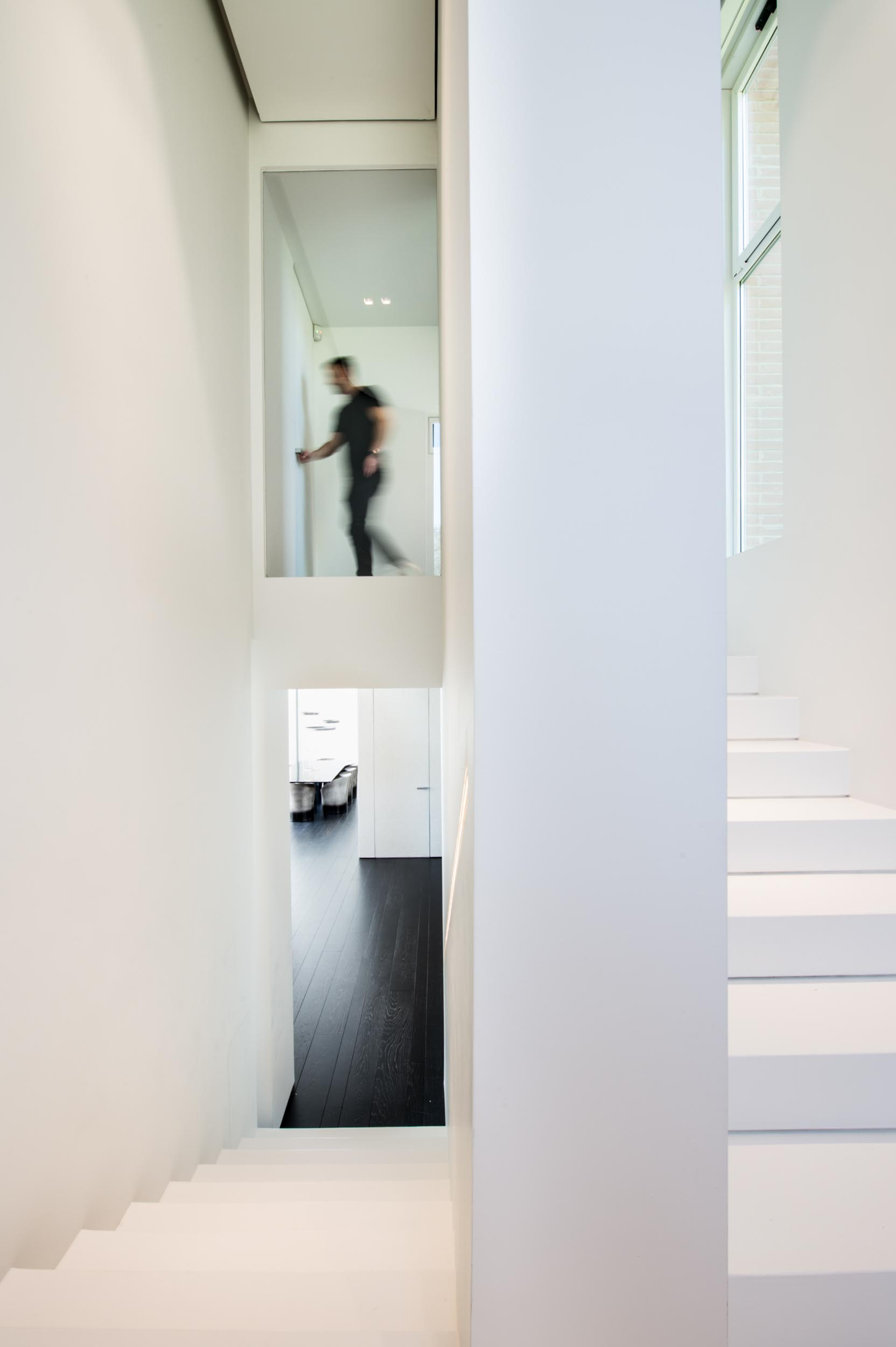 A white staircase that helps to keep the space bright, while a built-in handrail also has LED lighting hidden from view.