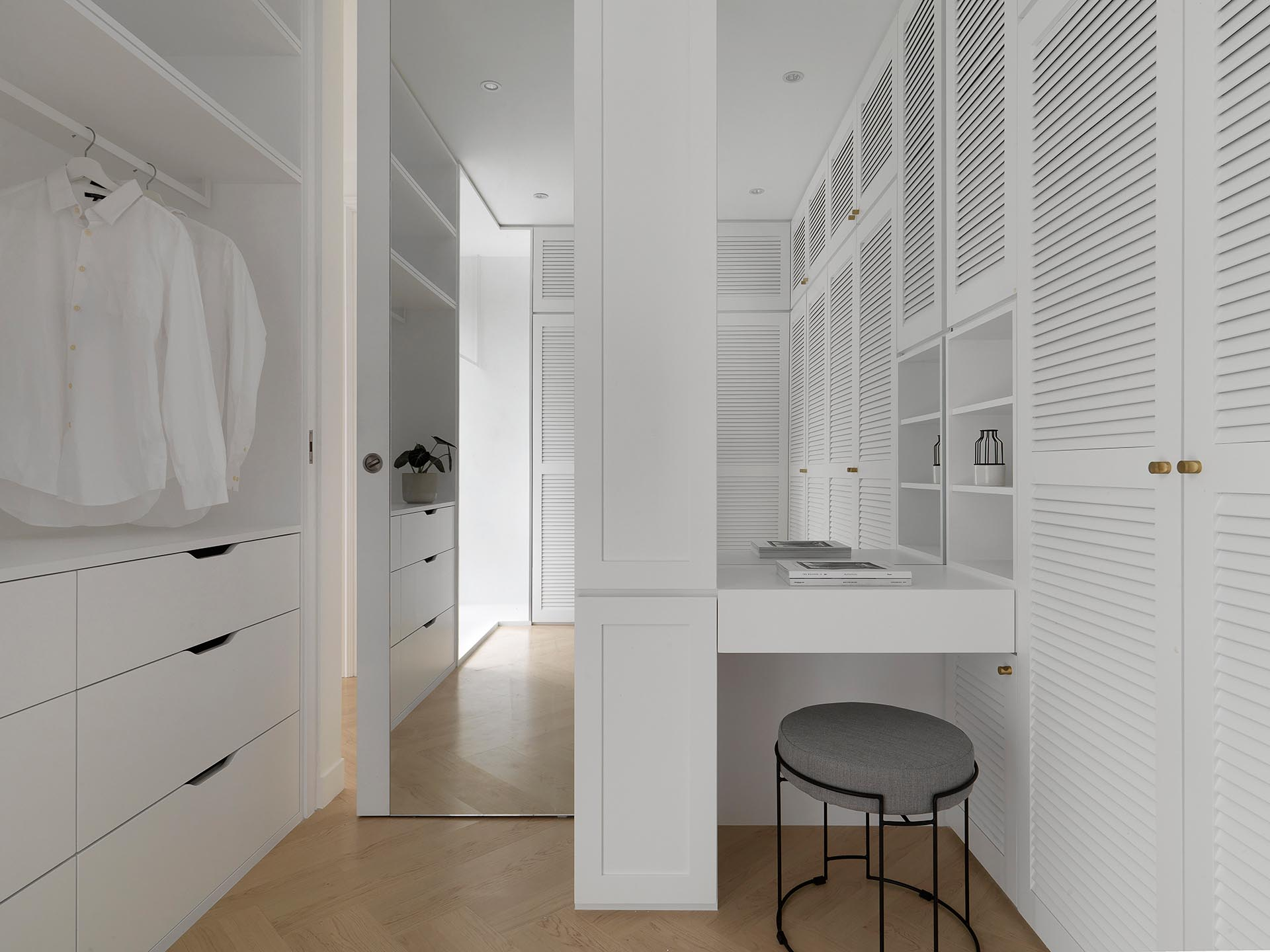 A modern walk-in closet designed with white cabinets, a small vanity, and floor-to-ceiling mirror behind the door.
