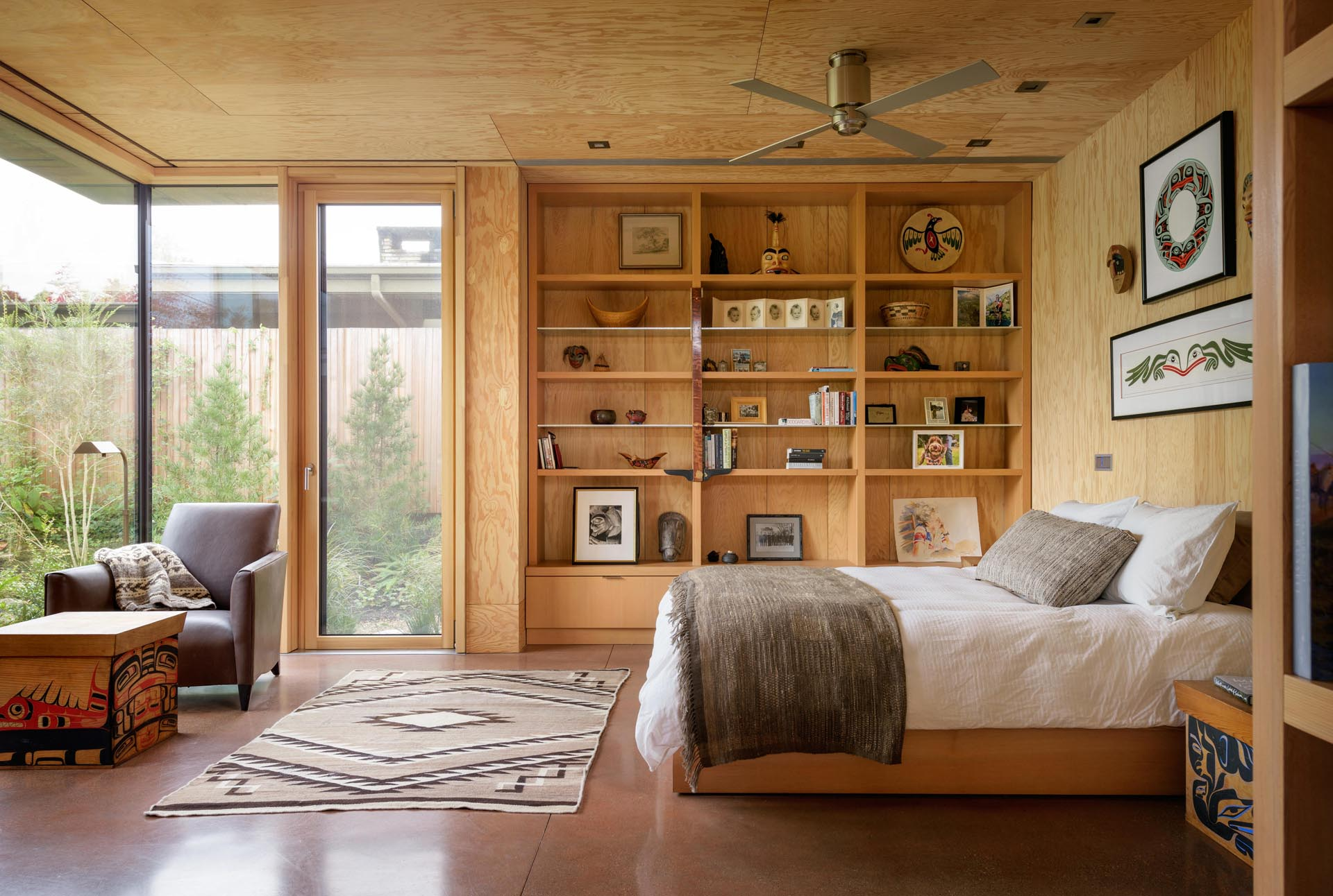 A bedroom with concrete floors and wood shelving.