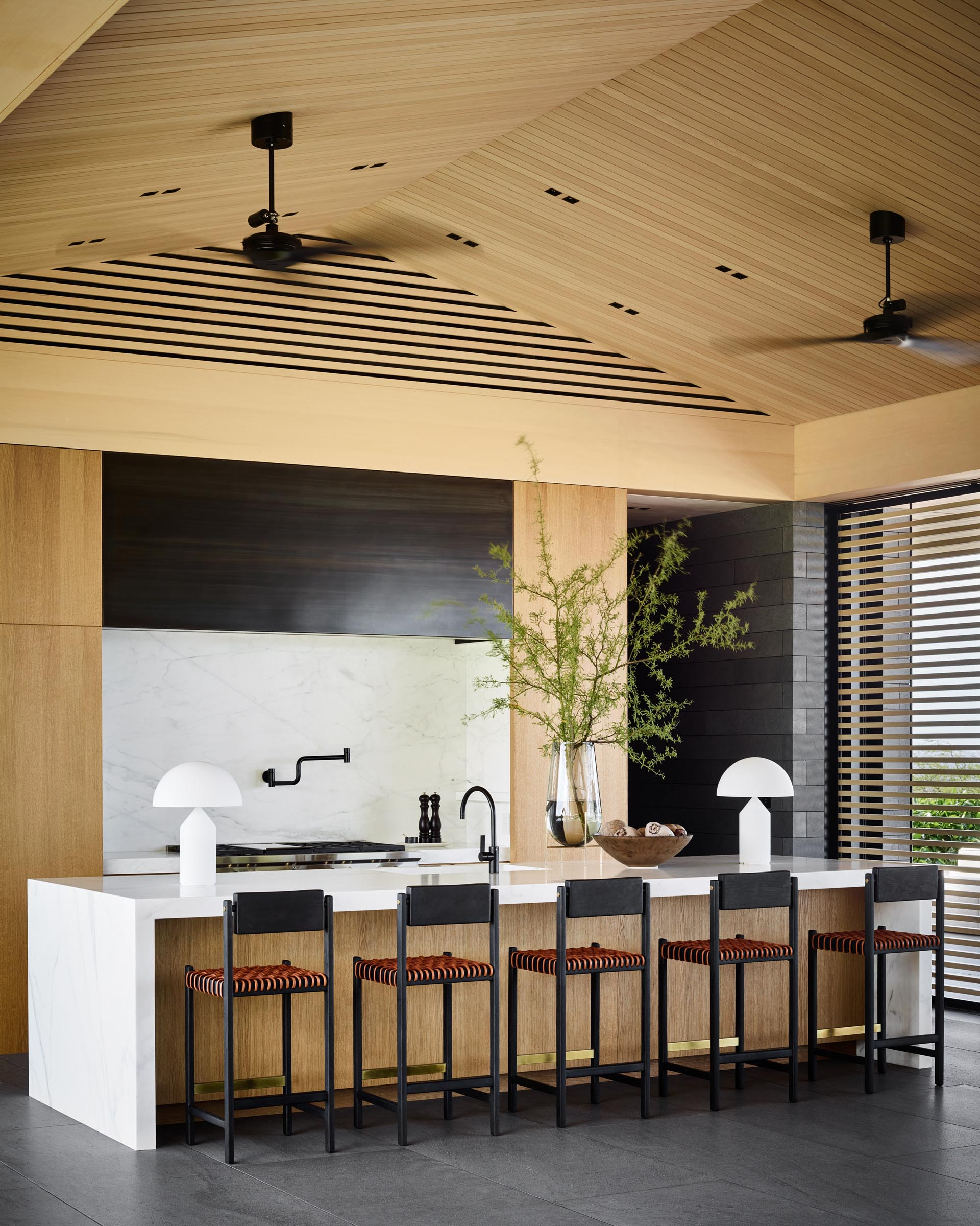 This modern kitchen includes a large island with room for seating and a waterfall countertop. Behind the kitchen, there's a walk-through pantry with wood cabinets and open shelving.