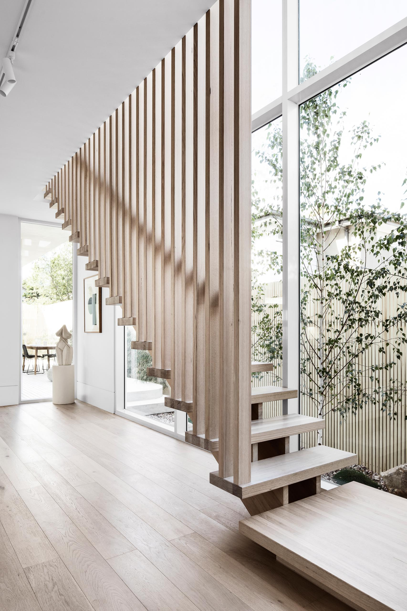 This modern staircase was located beside a wall of windows and has an overall muted, minimalist, light theme that was achieved by using natural Victorian ash timber on the treads and battens.